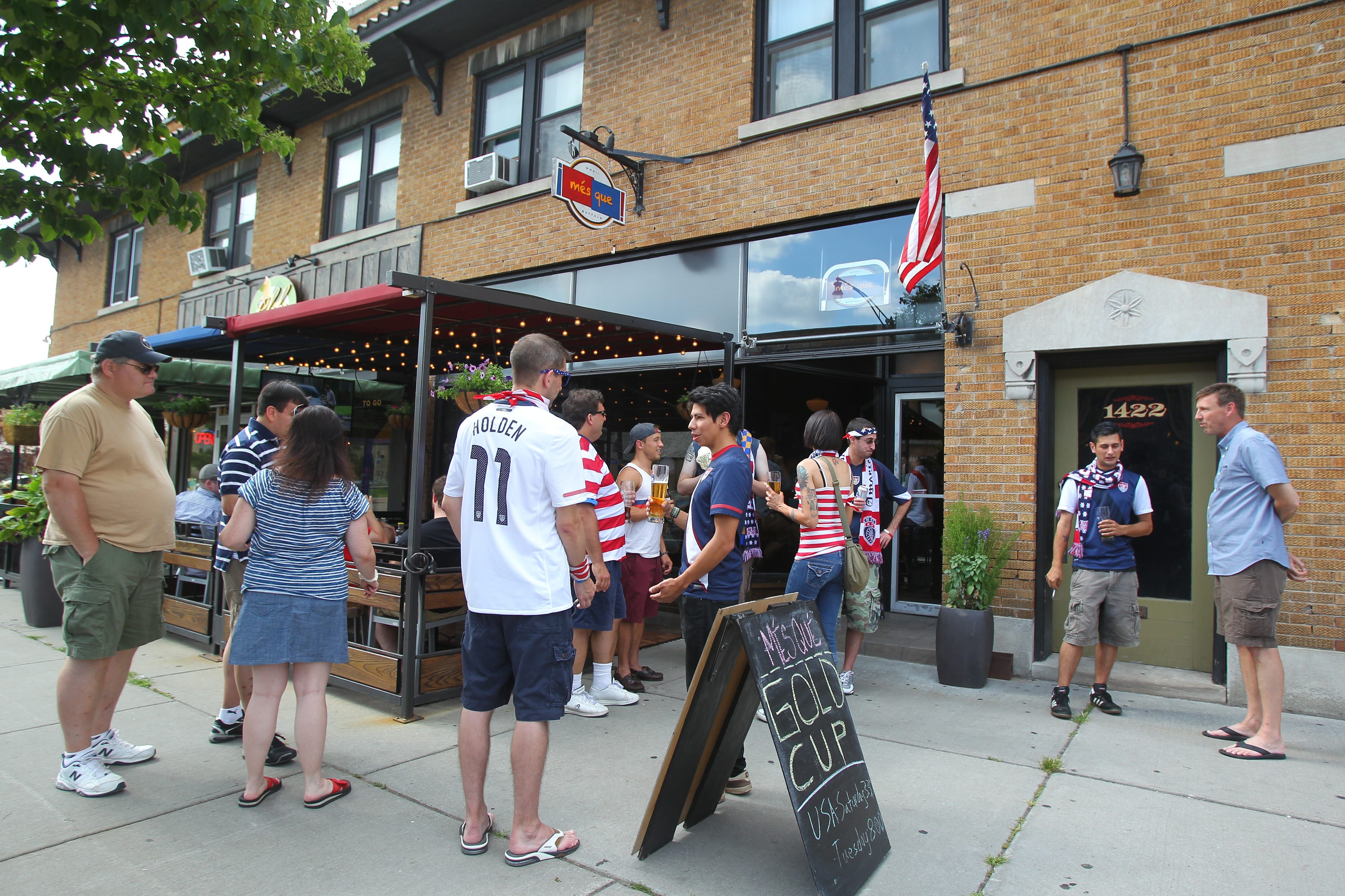 People mingle outside of Mes Que on Hertel Ave in Buffalo at the half of the USA vs. Cuba soccer game Saturday, July 13, 2013.  (Mark Mulville/Buffalo News)
