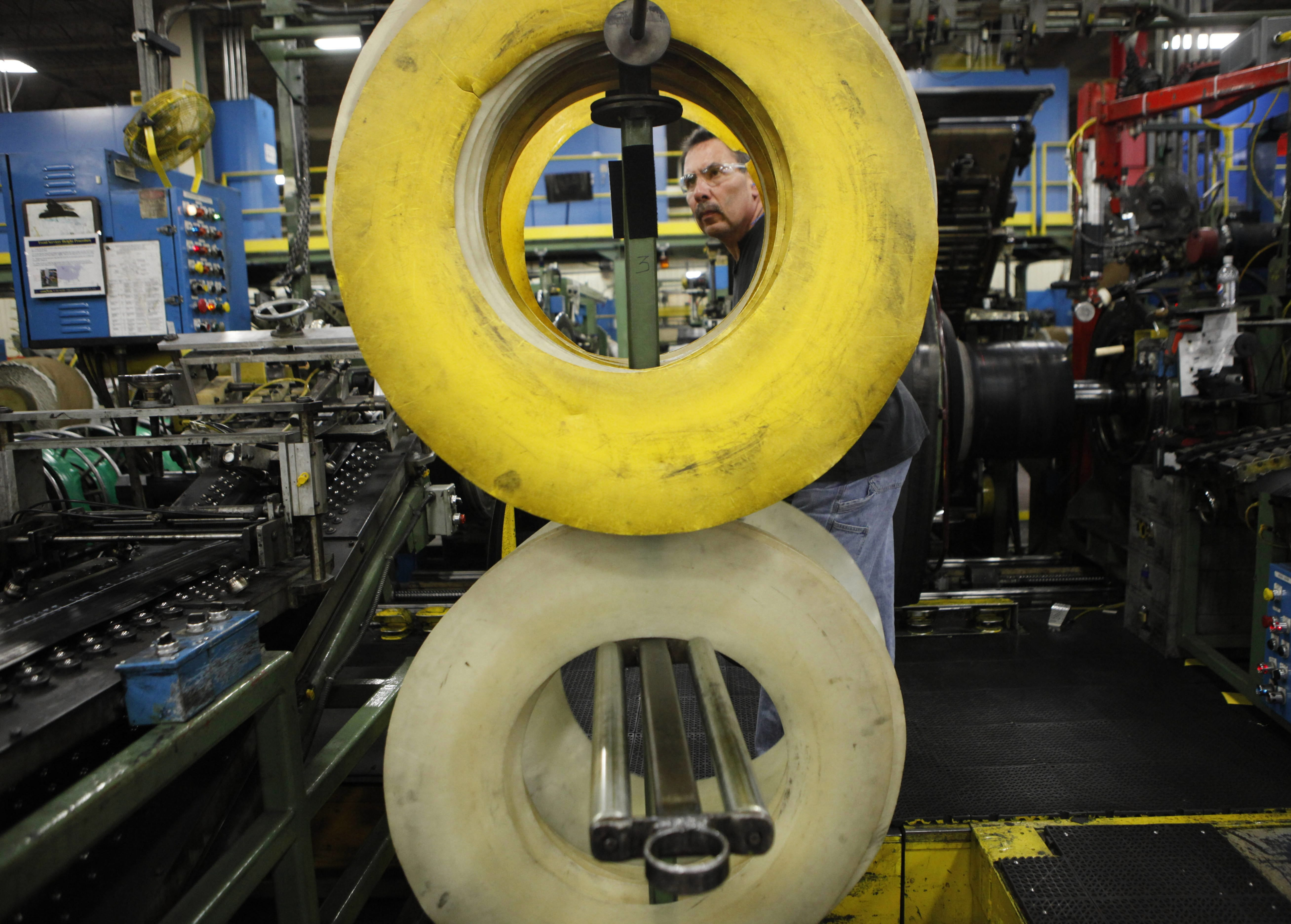 """A tire builder is framed by a rack of """"beads"""" as he works at the Goodyear Dunlop Tires North America plant in the Town of Tonawanda."""