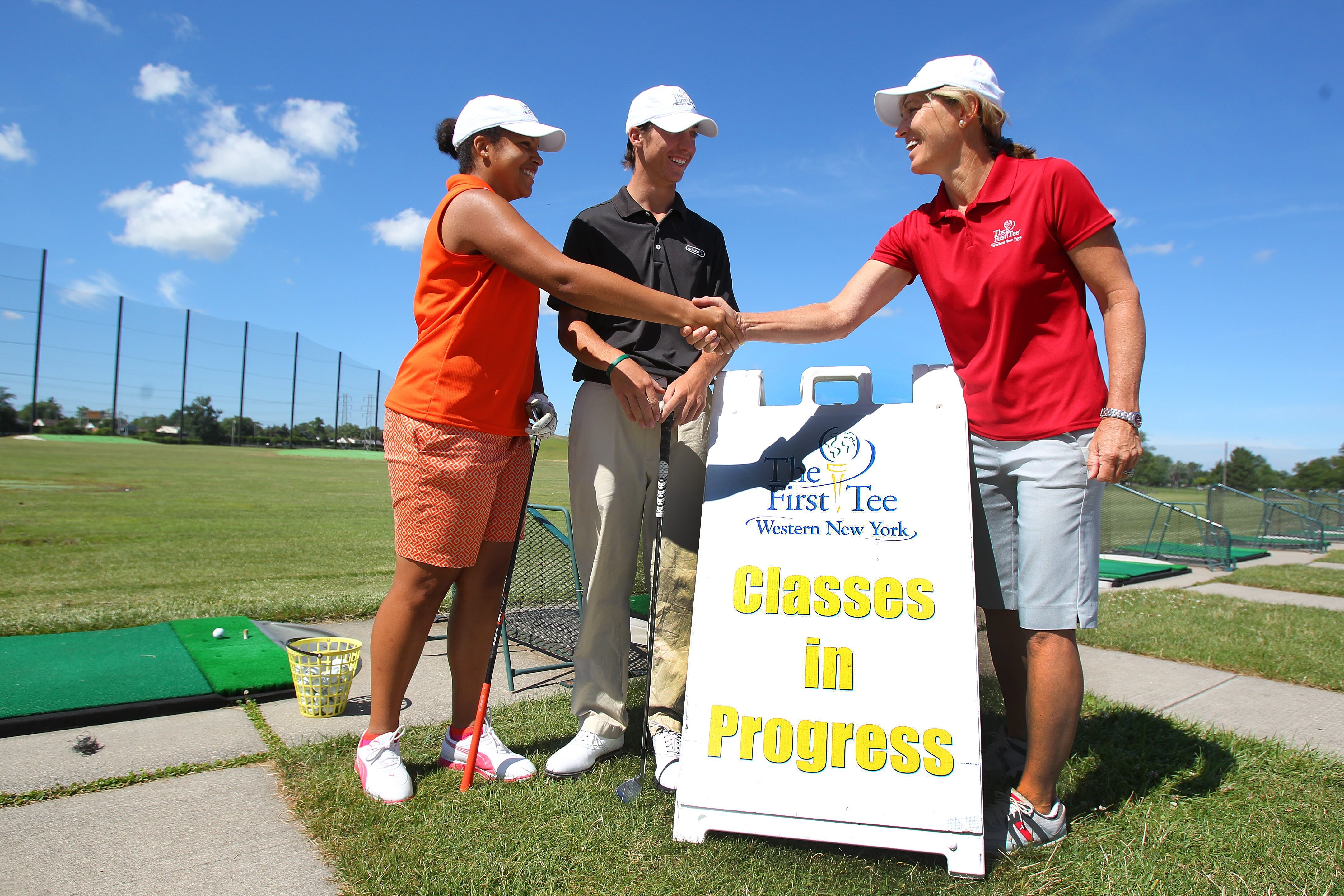 First Tee instructor Patty Jordan-Smith, right, greets Helen Busch and Gregory Sibick at the Brighton Driving Range in Tonawanda. Sibick and Busch both earned coveted playing opportunities.