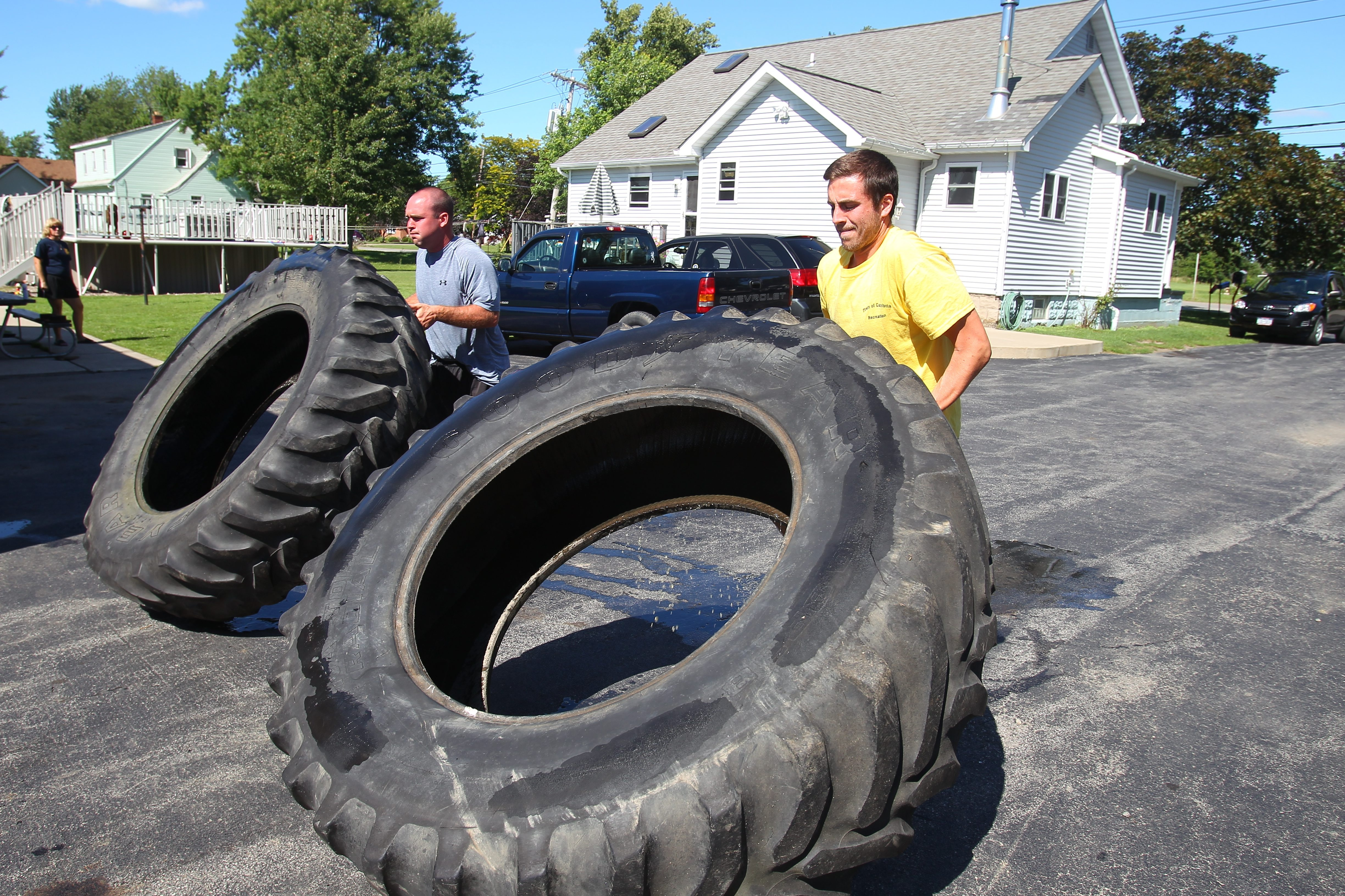 Matt Bove, right, and Andrew Donner flip tires that weigh between 350 to 400 pounds to prepare for the Tough Mudder competition.