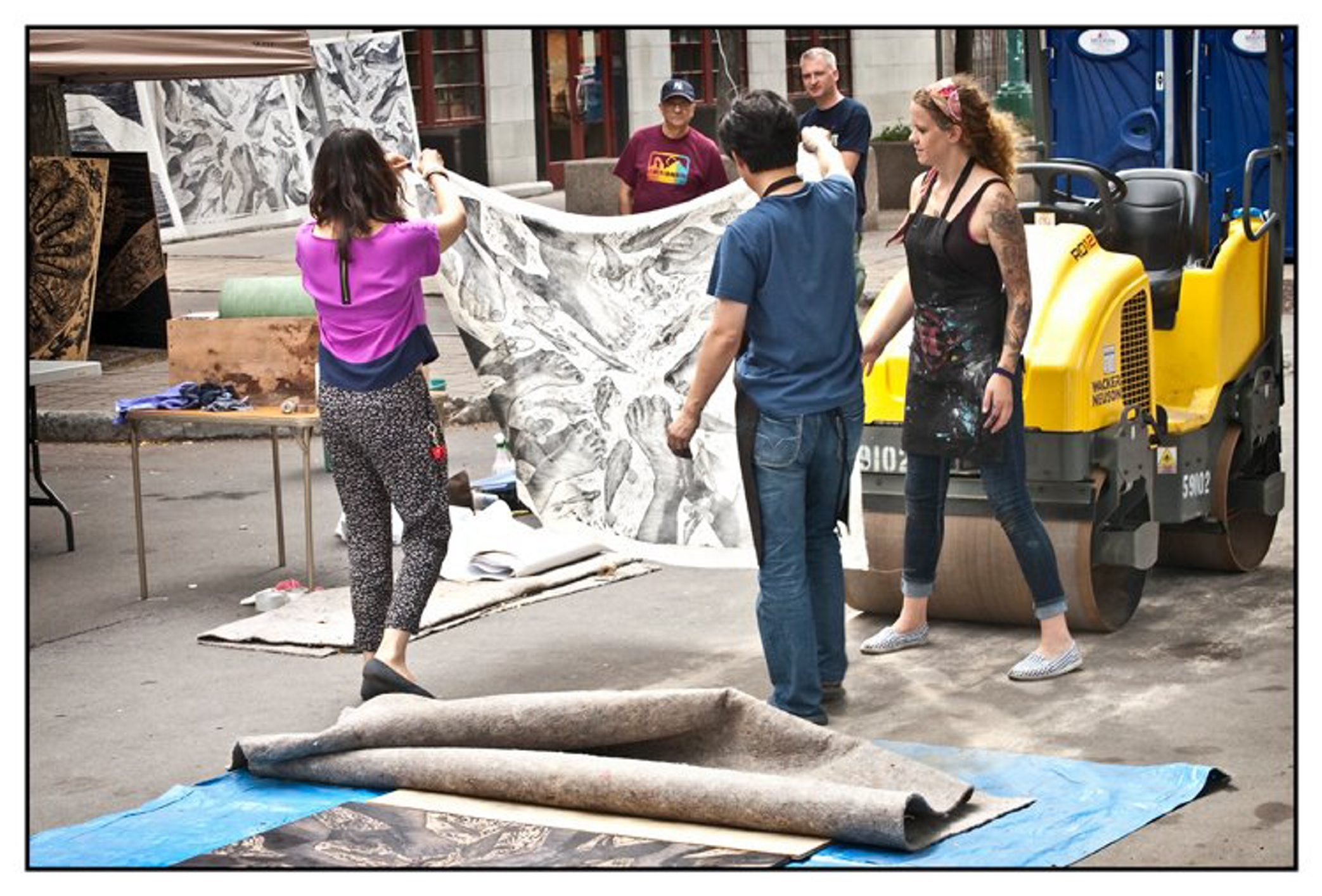 Visitors to the Western New York Book Arts Center hold up a print made with a steamroller on the center's sidewalk in 2012 during its annual Buffalo Book Fest.