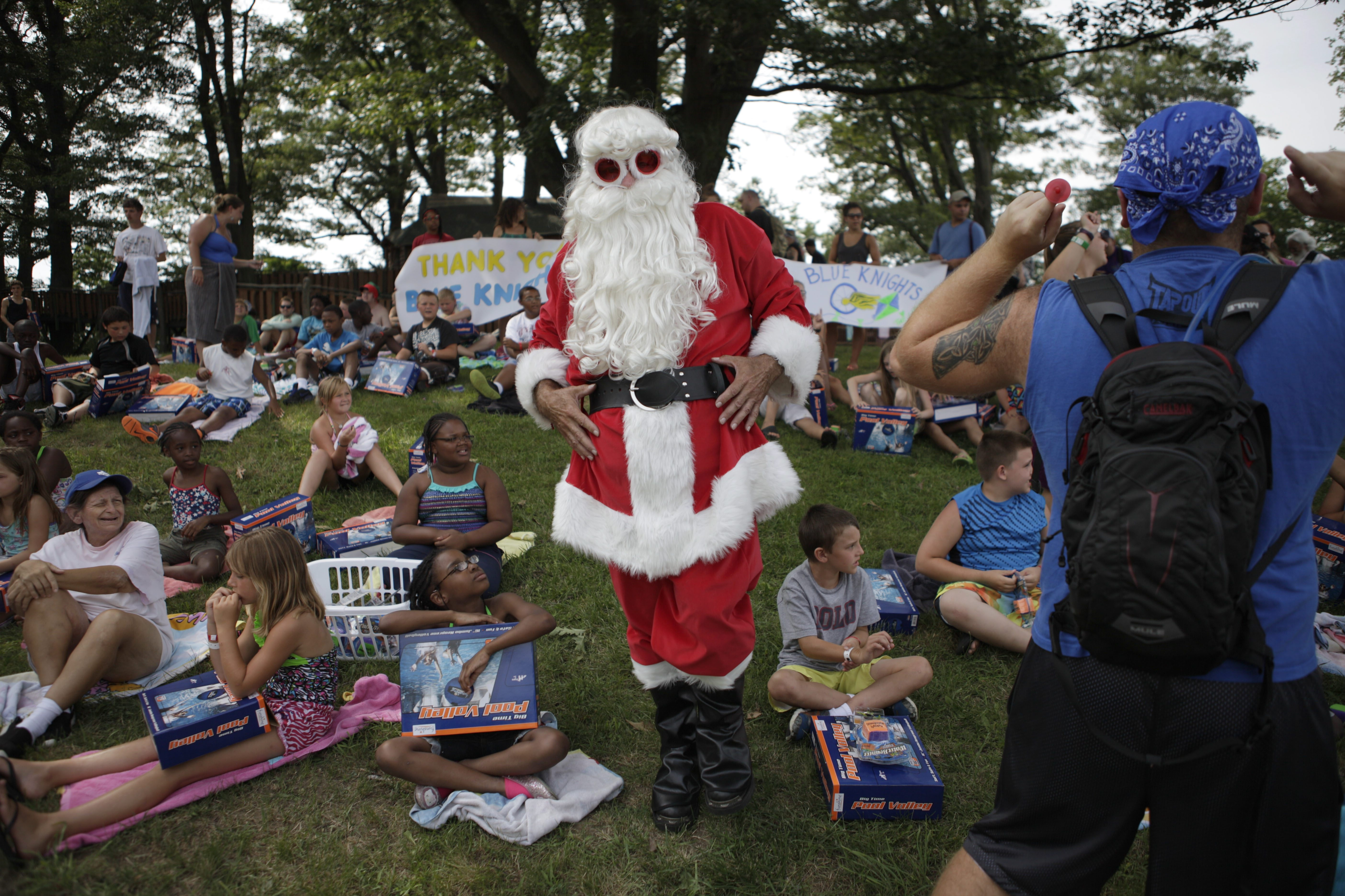 Santa Claus finishes passing out presents during a Christmas in July celebration Sunday at Cradle Beach in Angola. Below, the Blue Knights motorcycle club arrives at camp to deliver presents, to the delight of the young campers.