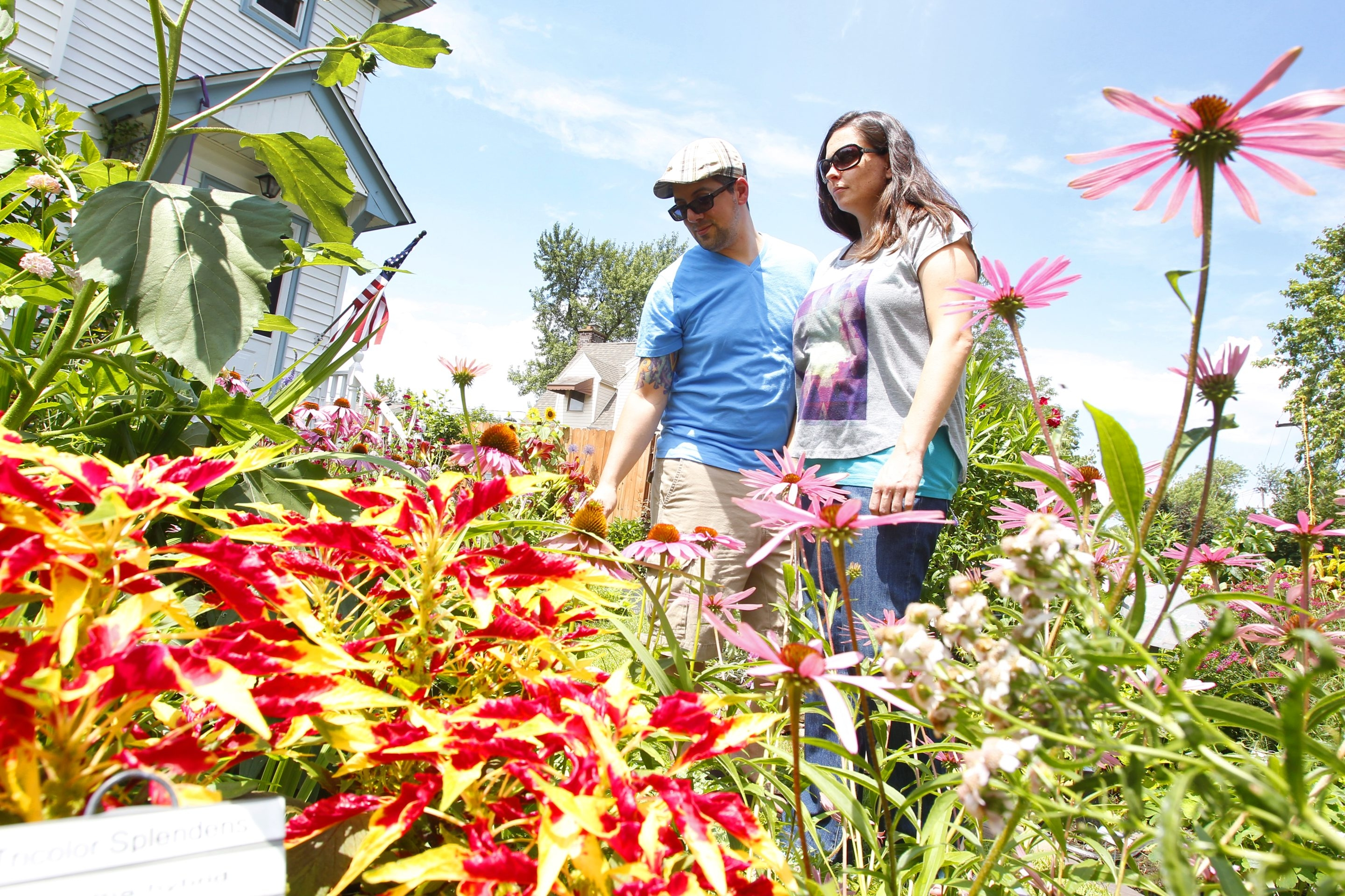 Jaime Shilen, and his wife, Jennifer, look over flowers at a home on Delaware Road in Kenmore on Saturday.