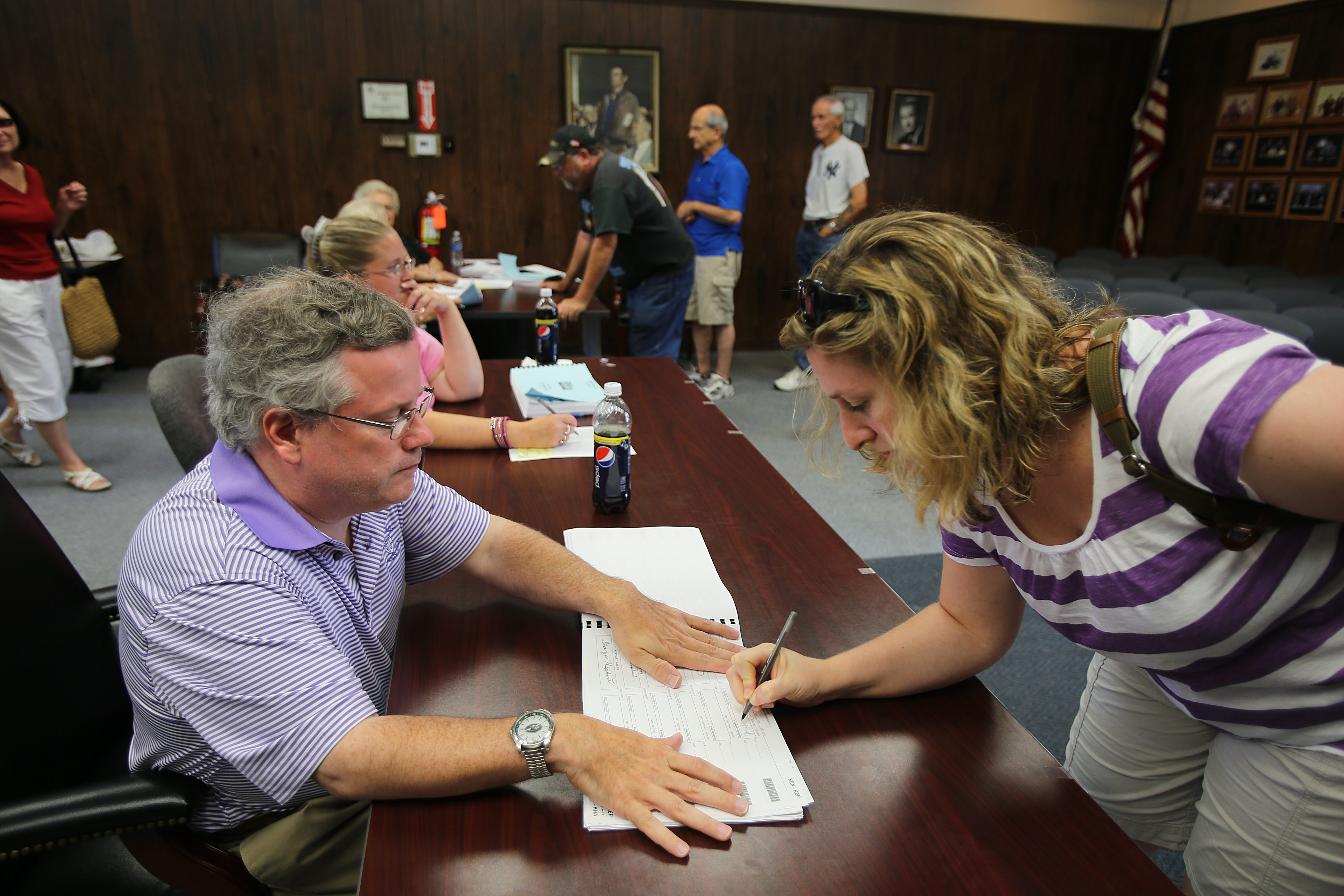 Jennifer Kensinger, of the Town of Lewiston, right, is signed in to vote by election inspector Daniel Vitch in Lewiston Town Hall.