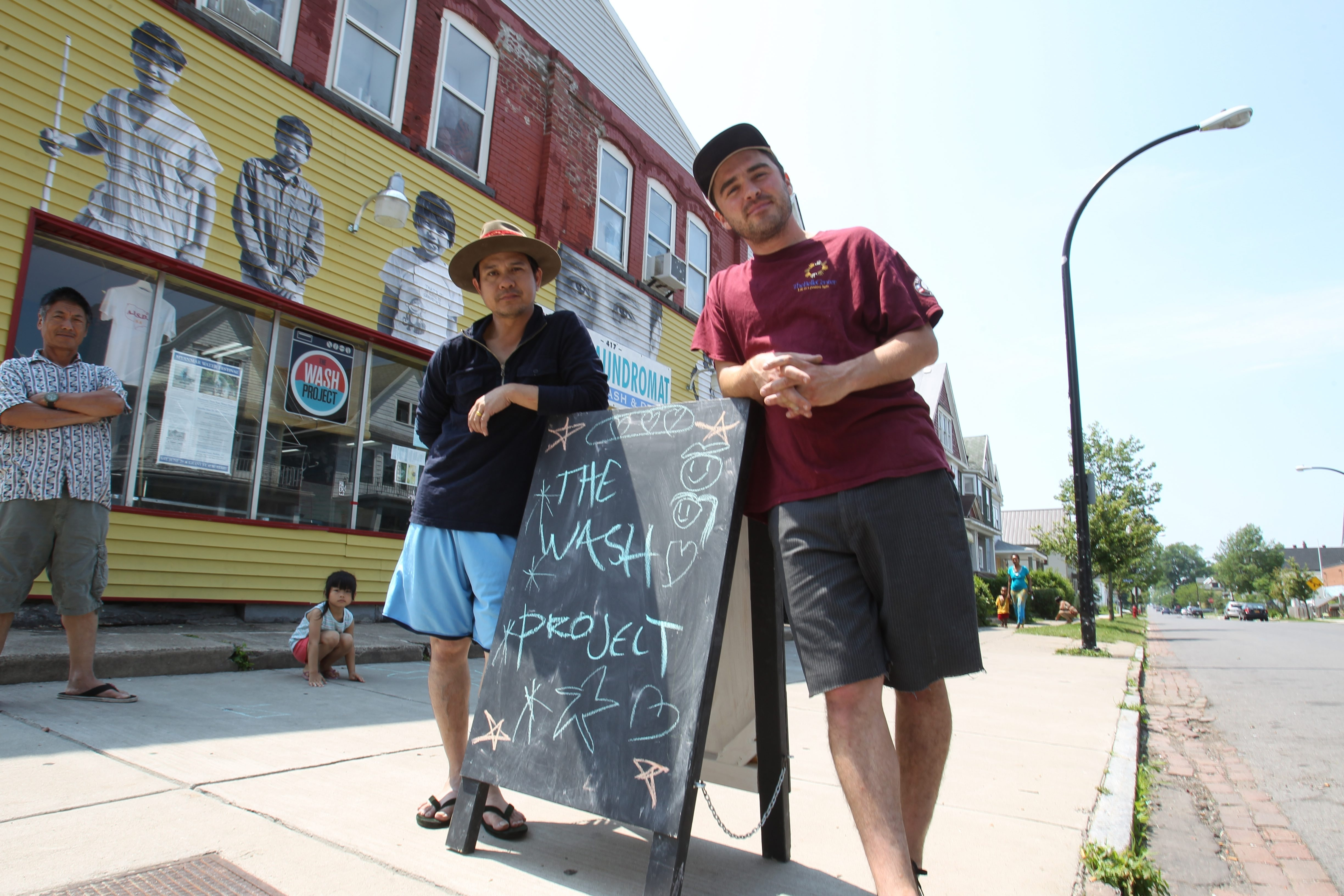 Barrett Gordon, in the red shirt, the coordinator of the WASH Project, poses with the laundromat's owner, Zaw Win, at Westside Value Laundromat on Massachusetts Avenue in Buffalo on June 24.