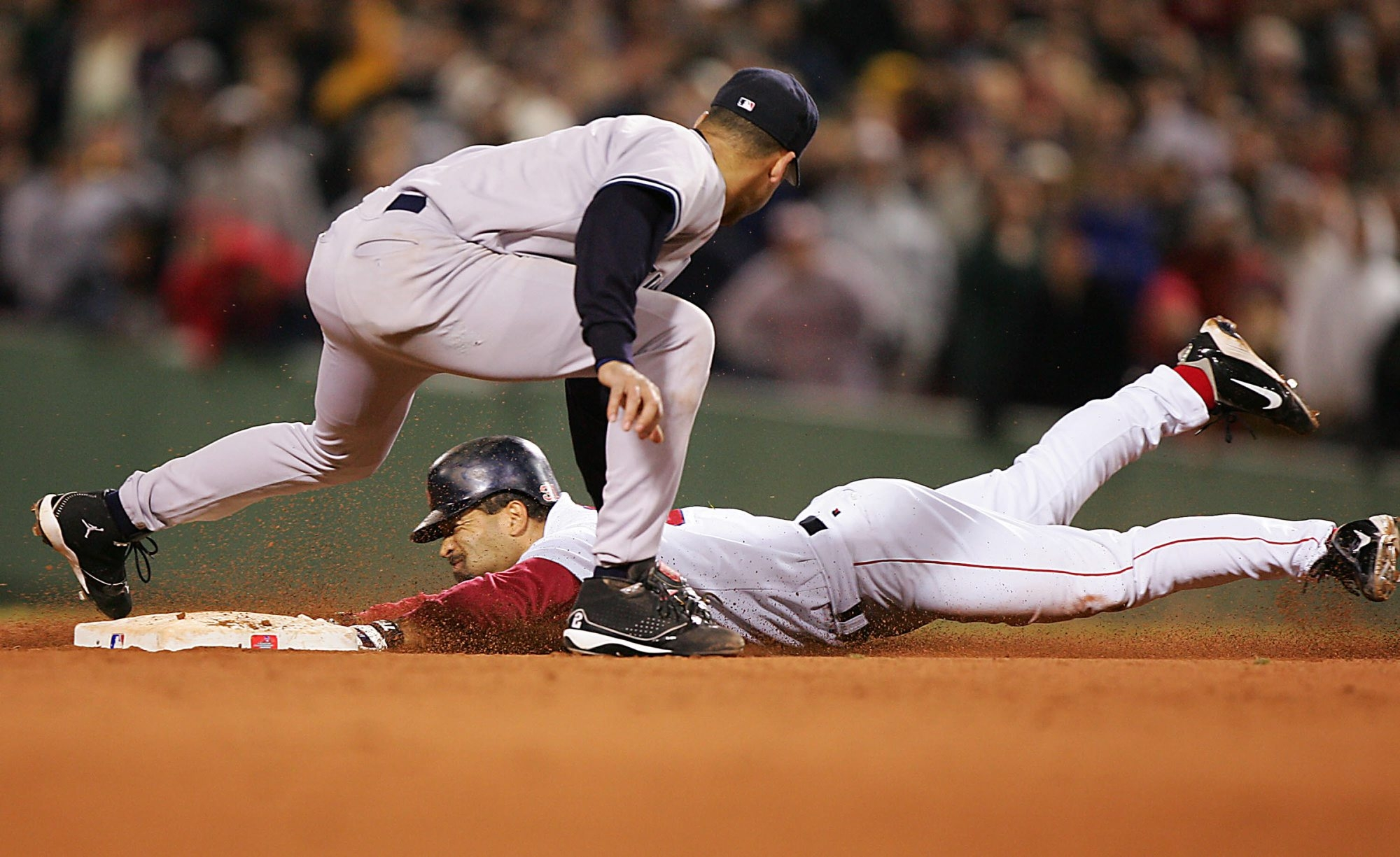 Dave Roberts steals second for the Red Sox in Game Four of the 2004 American League Championship Series.   Derek Jeter #2 of the New York Yankees applies the tag in the ninth inning during game four of the American League Championship Series on October 17, 2004 at Fenway Park in Boston, Massachusetts.  (Photo by Jed Jacobsohn/Getty Images)