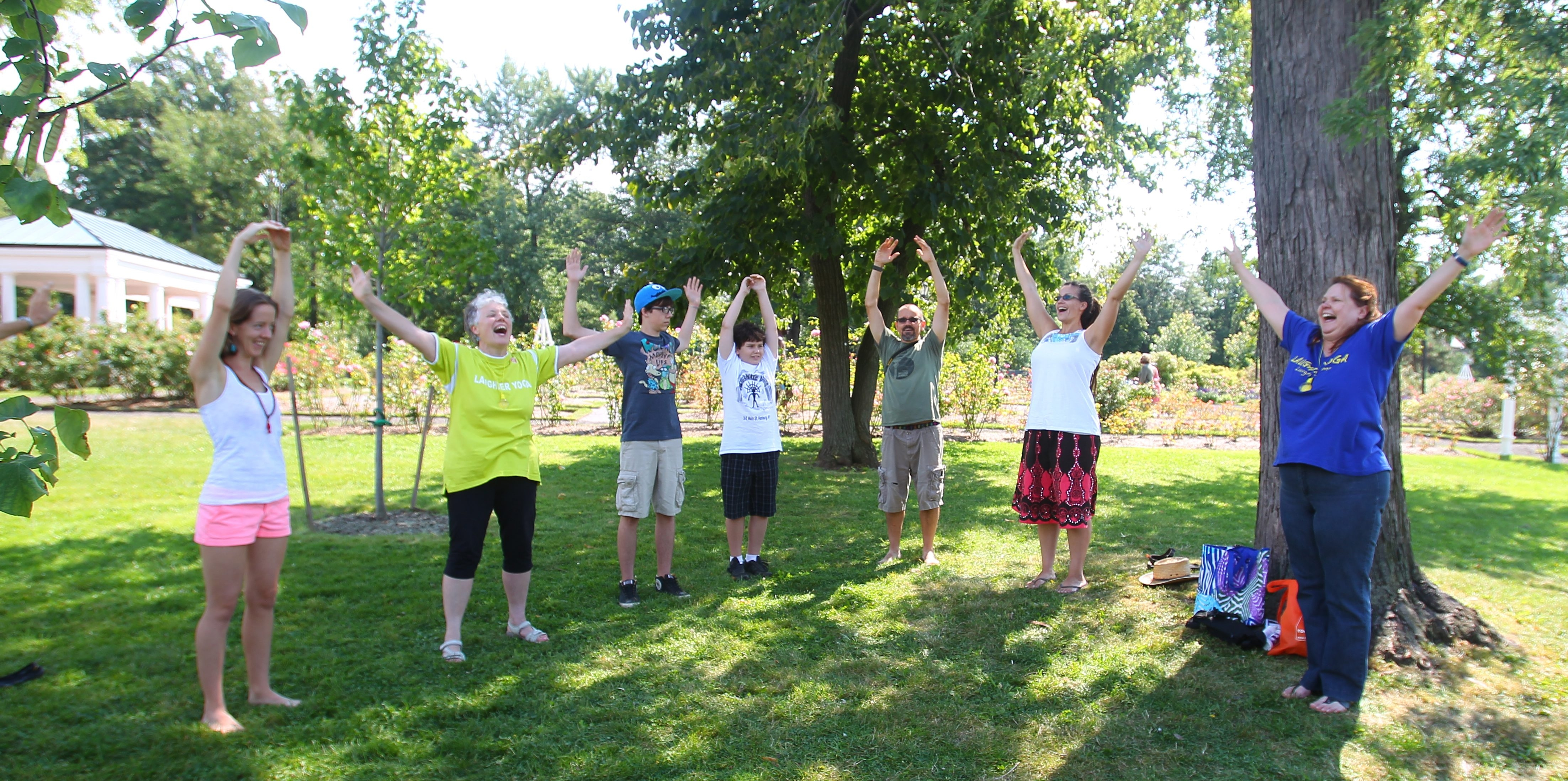 Participants try laughing yoga exercises at the Holistic Health Expo at Delaware Park's Marcy Casino on Sunday.  Practitioners say laughter yoga energizes them and awakens in them a sense of childlike joy.