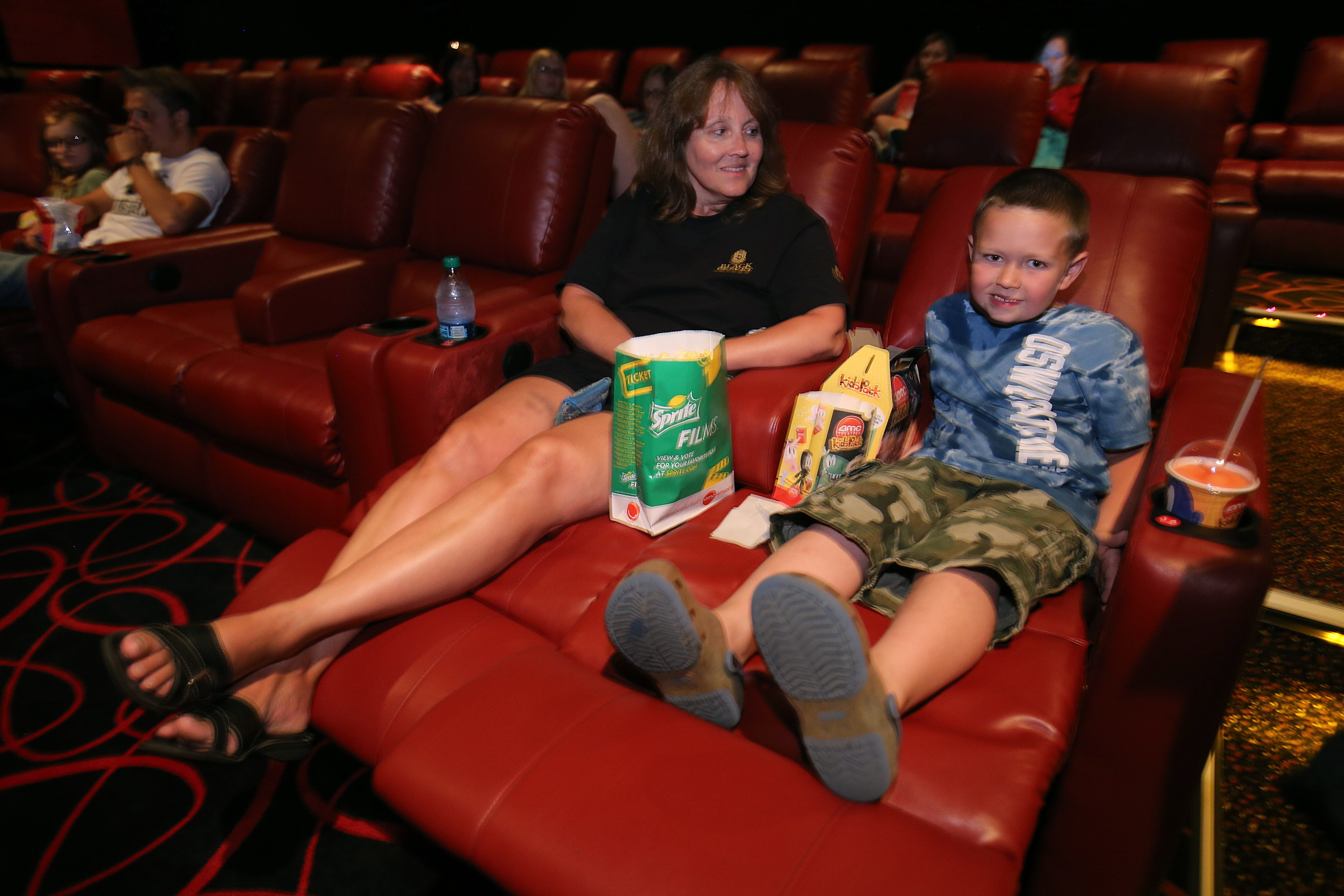 Phyllis O'Byrne, left, of Lockport, and her godson, Conor Crandall, 6, of Medina, enjoy the reclining leather seats at the AMC Maple Ridge movie theater.