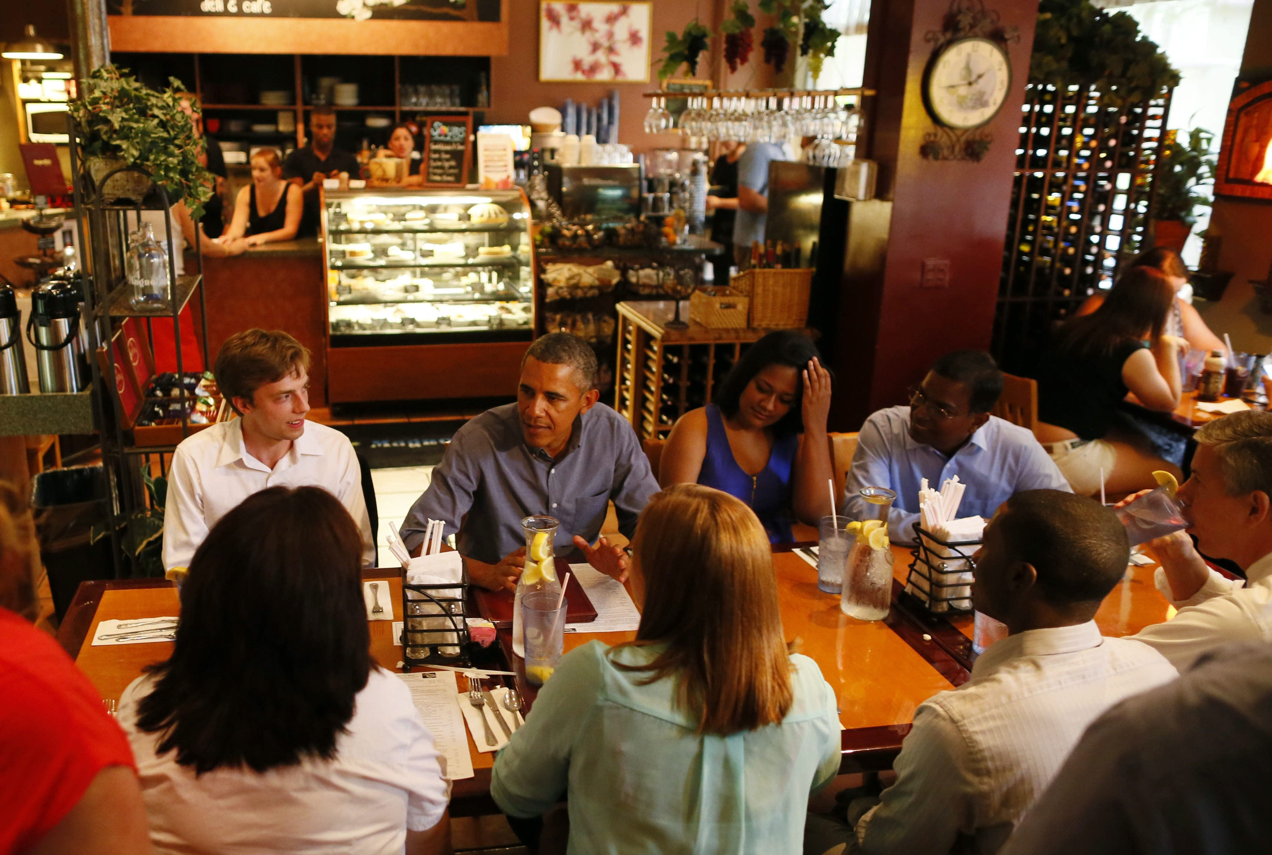 President Obama sits down with University of Rochester students for a roundtable discussion during an unscheduled stop Thursday at Magnolia's Deli and Cafe in Rochester. Sitting with Obama are, from left, Doug Brady, Wesline Manuelpillai and Peter Manuelpillai. Obama's New York bus tour Thursday also included Buffalo and Seneca Falls.