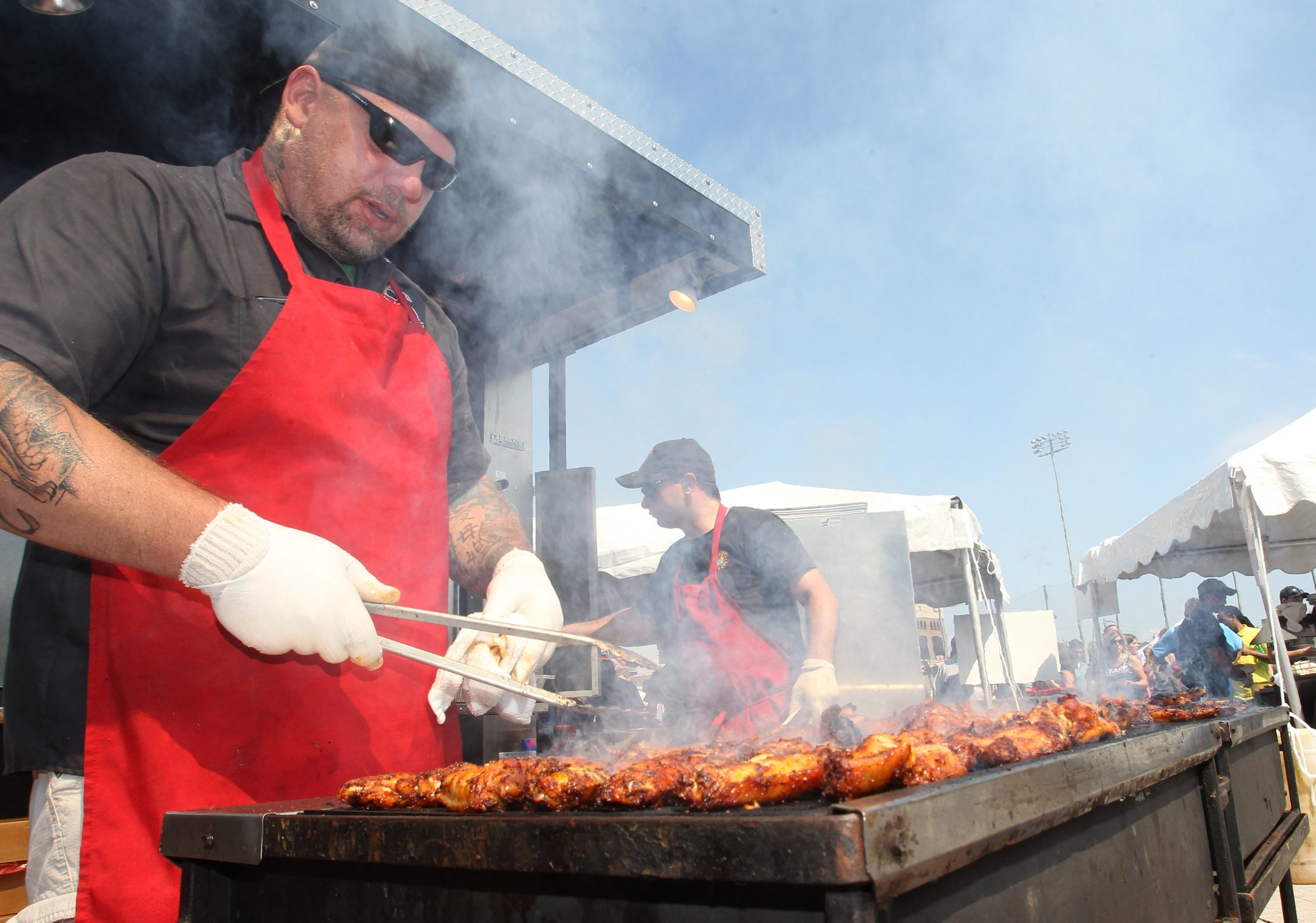 Jason Holly grills chicken wings at the 12th annual National Buffalo Wing Festival at Coca-Cola Field on Saturday. Visitors came to the festival from 44 states and every continent but Antarctica.