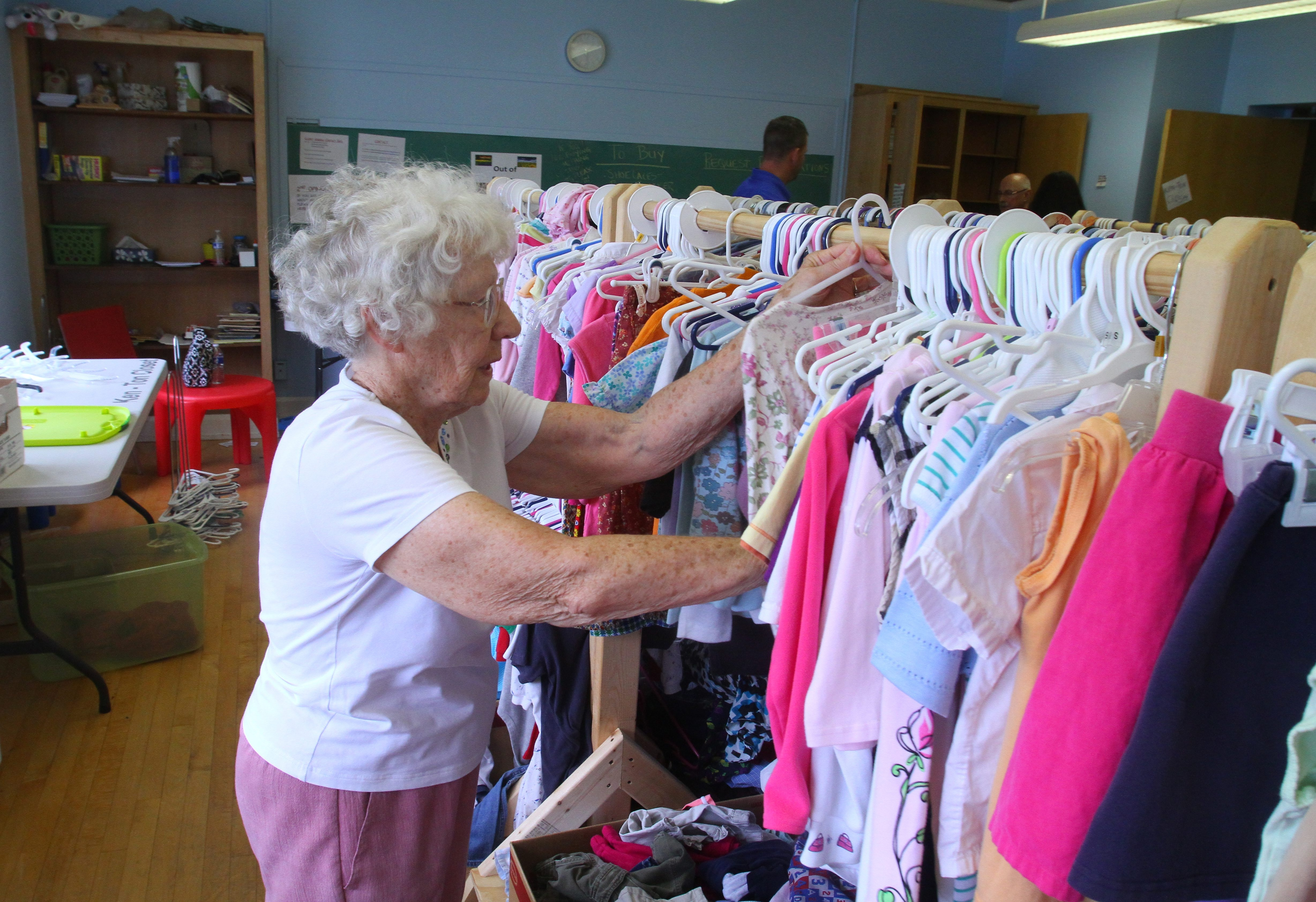 Dorothy Smatresk, a volunteer at the Ken-Ton Closet, organizes clothing at the Town of Tonawanda center Friday. Thieves stole hundreds of dollars worth of donated school supplies last week, but generous donors have more than made up for what was taken.