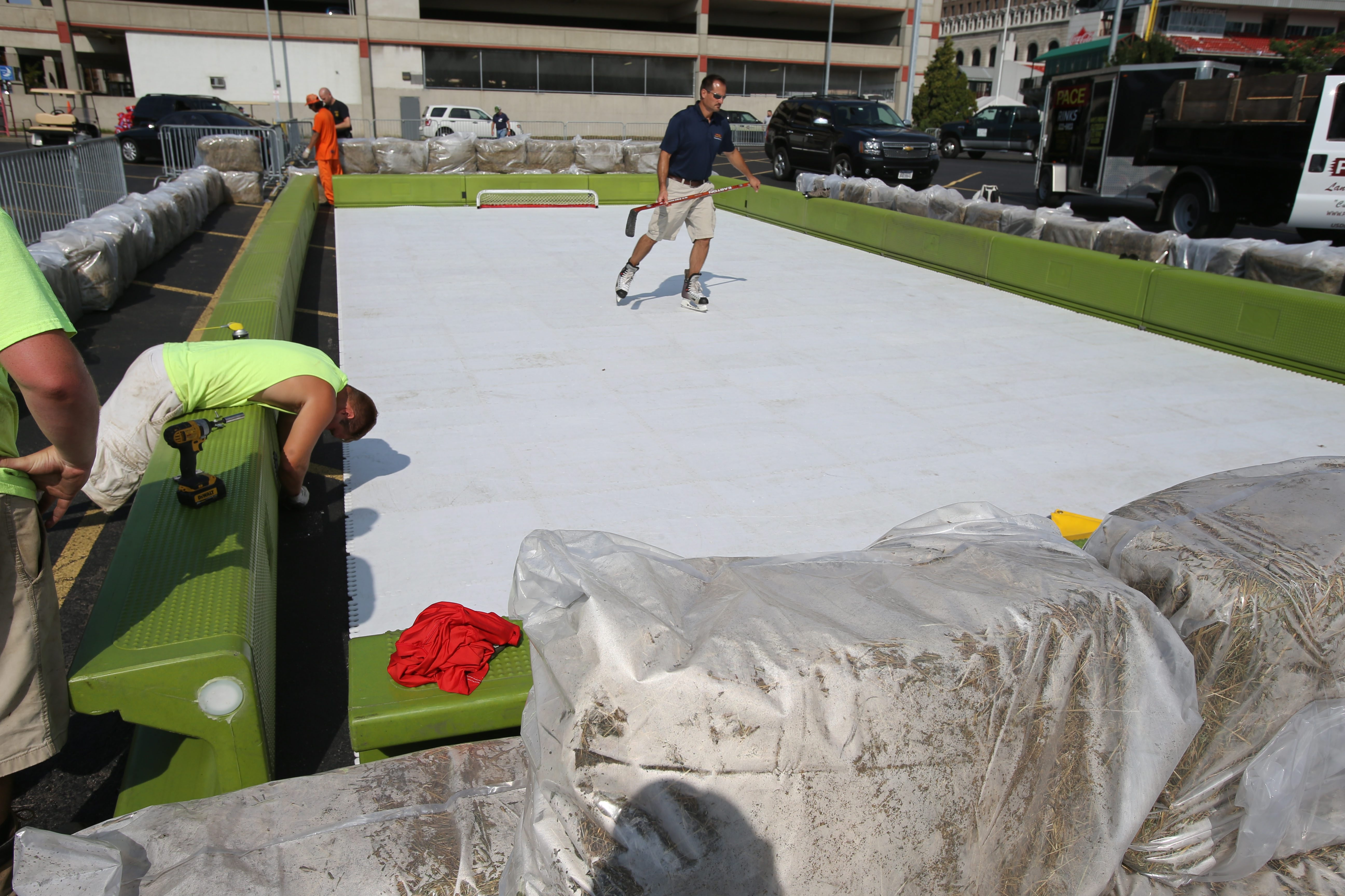 Mike Pace, owner of Pace Landscaping and Ice Rinks in Hamburg, skates on a Can-Ice artificial surface rink in the parking lot behind Coca-Cola Field, as workers assemble it in preparation for the Labatt Blue Wingman Hockey Tournament.