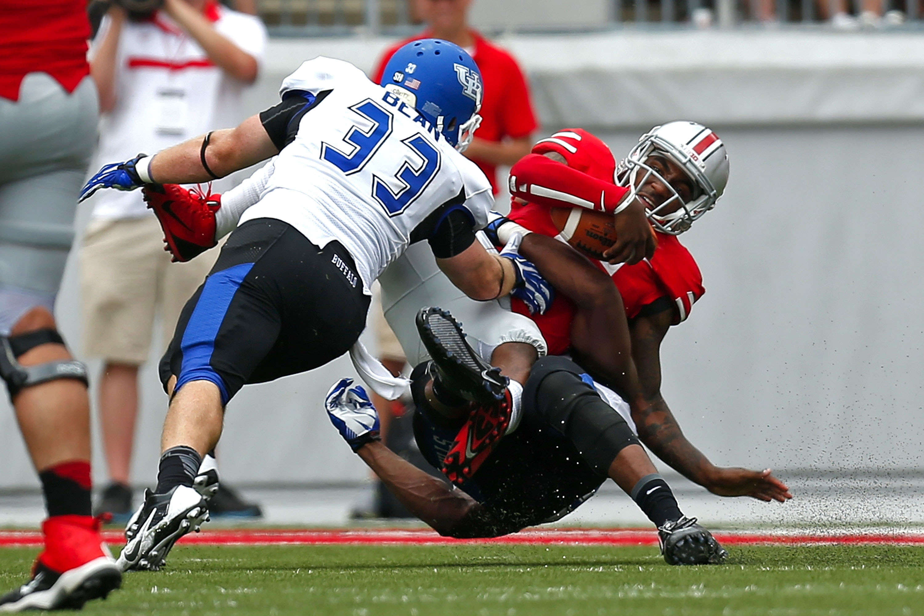 Braxton Miller (5) of Ohio State is sacked by UB's Khalil Mack (46) and Blake Bean (53) during Saturday's game in Columbus.