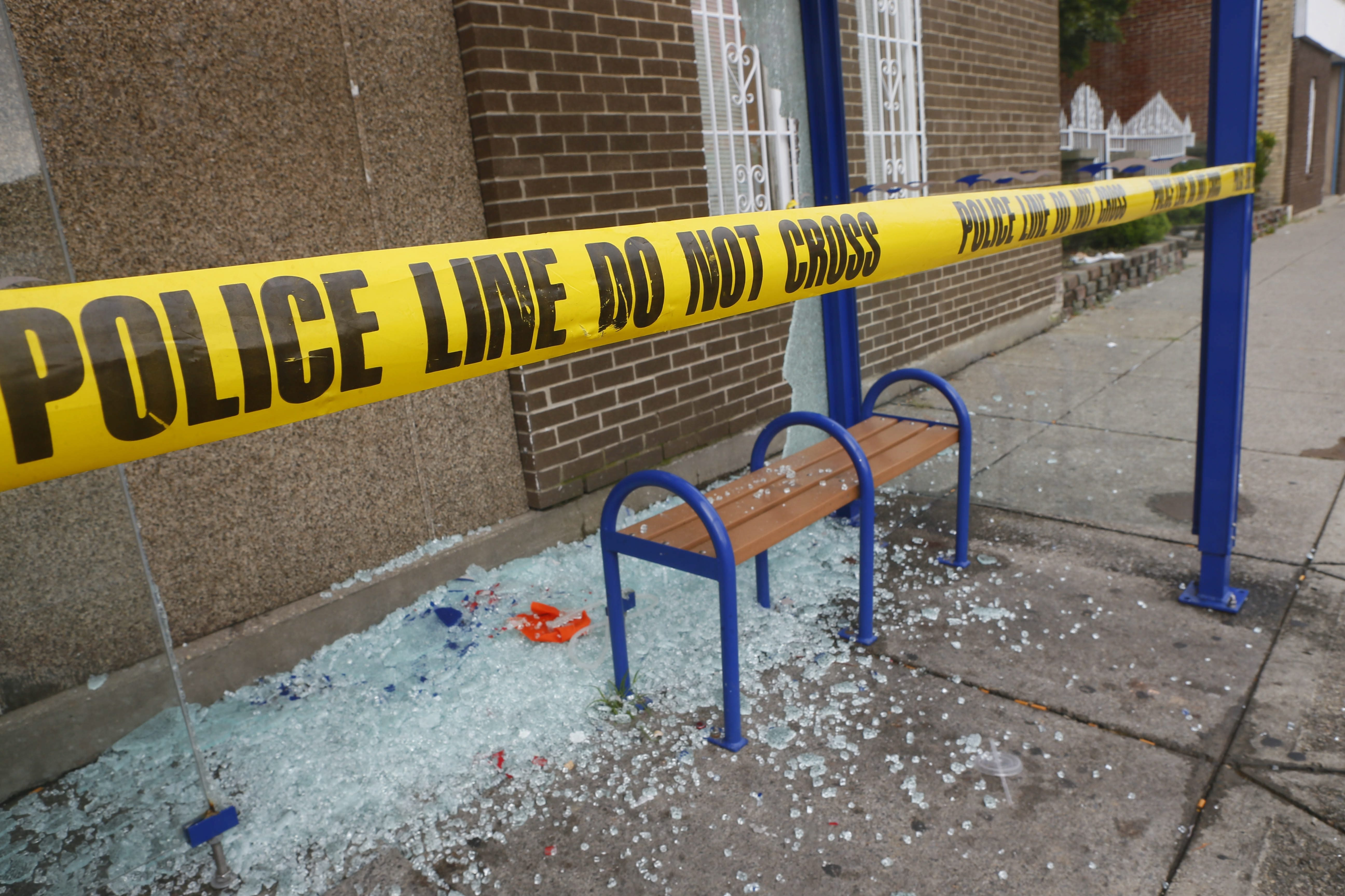 A large pile of broken glass remains Wednesday after vandals overnight damaged several bus stops on Grant Street.
