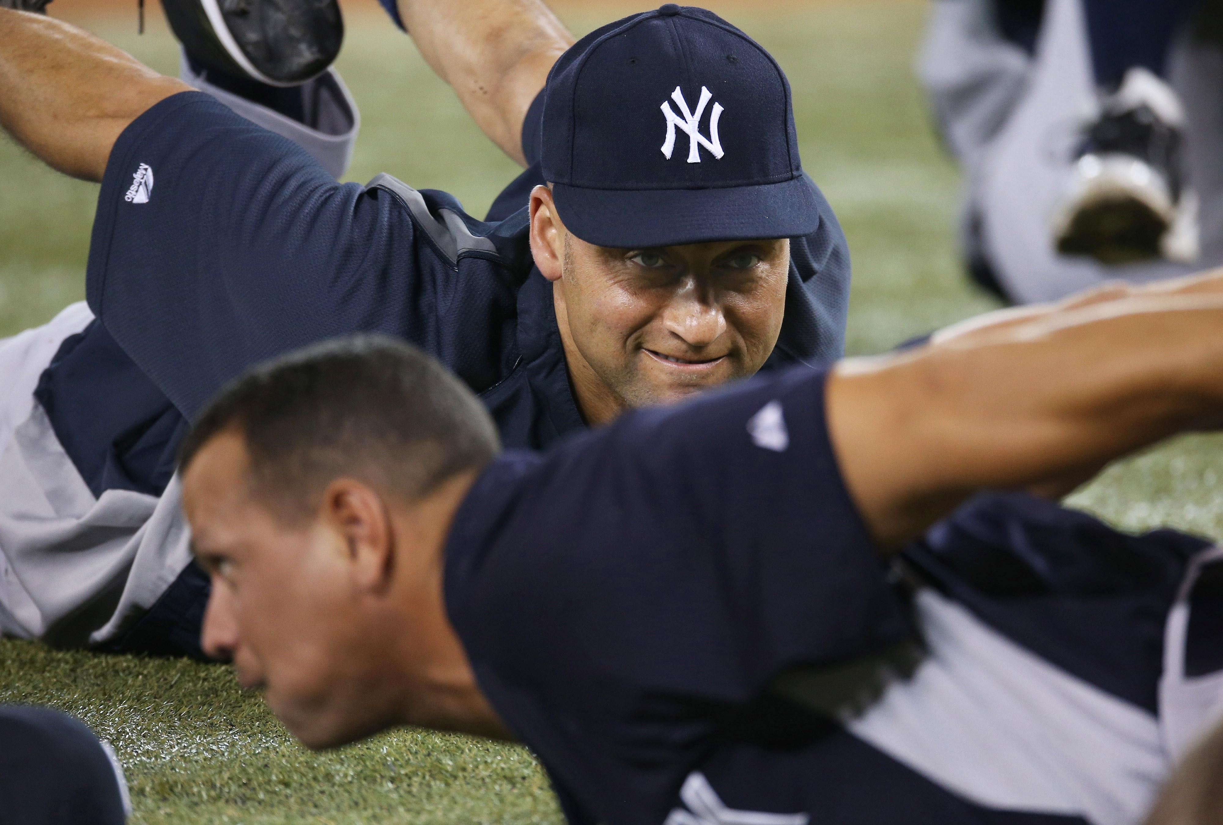 Derek Jeter stretches next to Alex Rodriguez prior to Monday's game in Toronto .