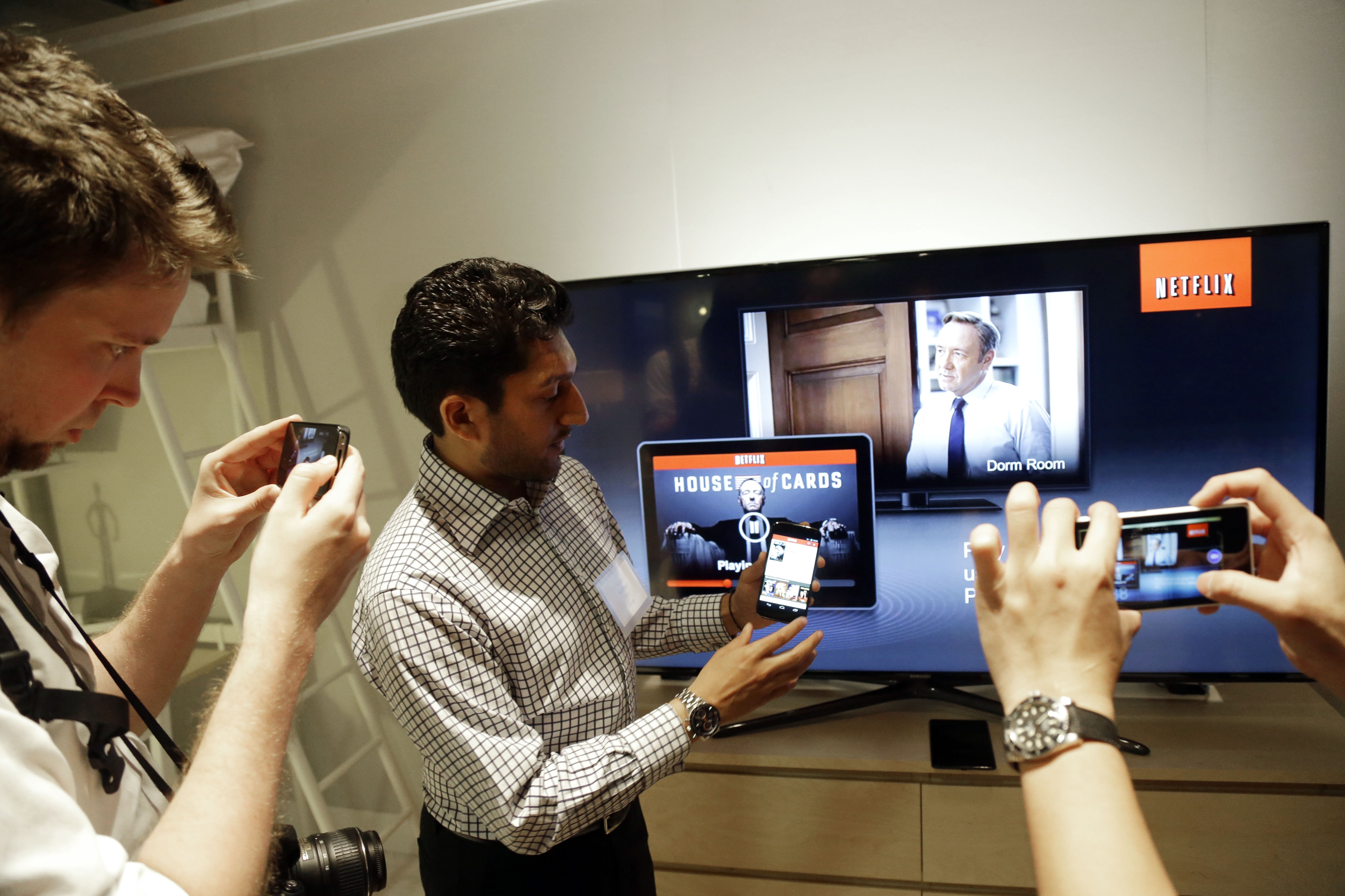Suveer Kothari, center, displays how the new Chromecast device operates a television with the use of a smartphone