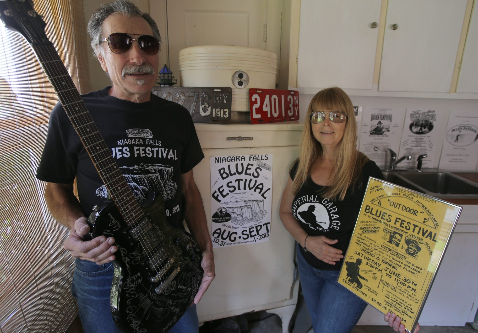 Sherry and Toby Rotella hold items that relate to their roles as organizers of the annual Niagara Falls Blues Festival, including a poster from the defunct Imperial Garage, a Niagara Falls bar that booked blues artists.