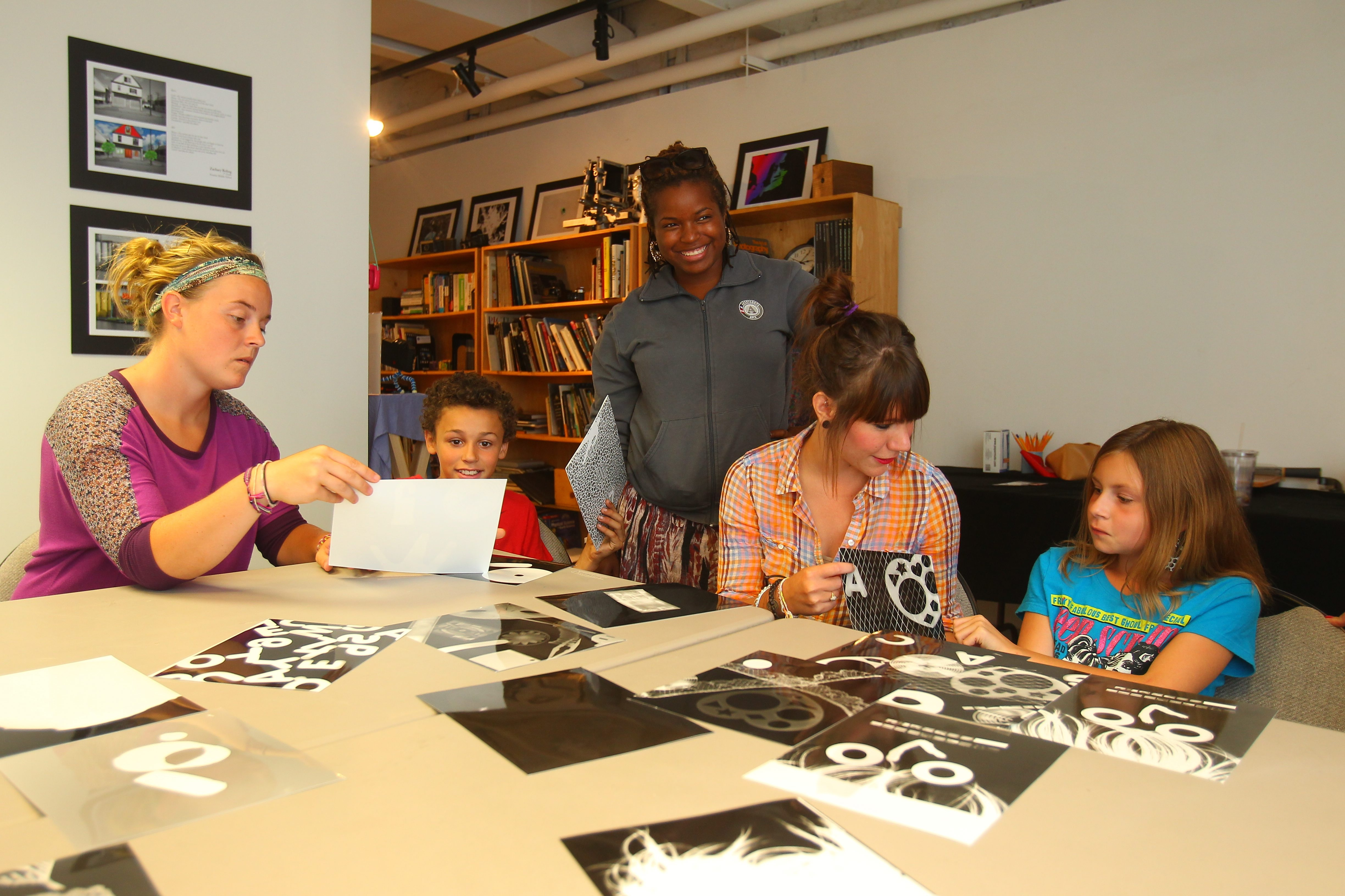 Project SOAR coordinator Jessica Johnson, left, works with Jeremiah Marquez, 11, of Buffalo, while coordinators Rasheena Turman and Karen Brady work with Alyssa Wolfson, 9, of Buffalo, as the students pick out photograms at CEPA Gallery.