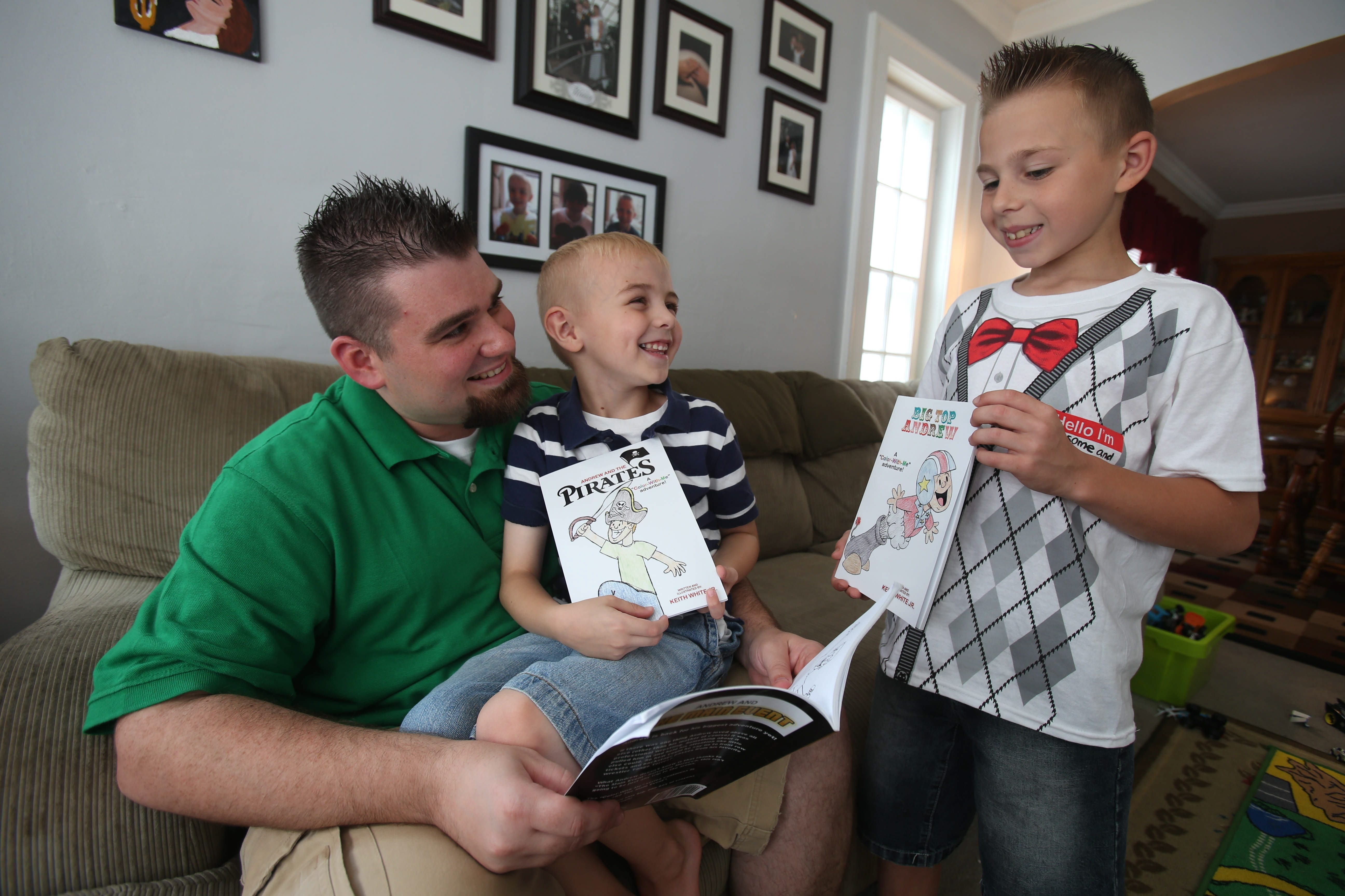 Keith White Jr., with Collin, 5, and Andrew, 10, right, has written short chapter books to help Andrew succeed in school. White hopes his books can be used by other children with reading problems.
