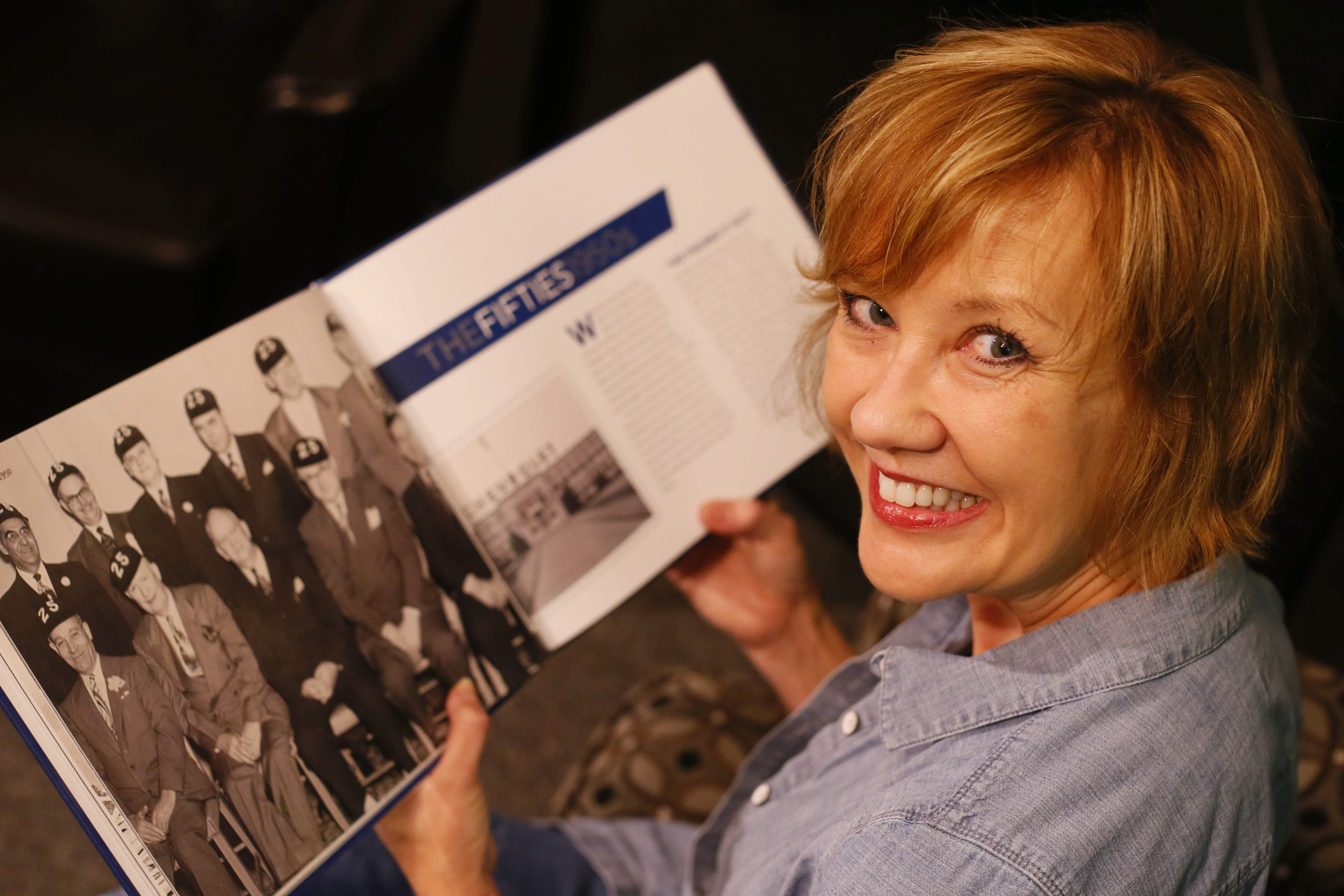 Annette Herrman pages through the book she wrote to mark the 75th anniversary of the GM Powertrain Tonawanda Engine Plant.