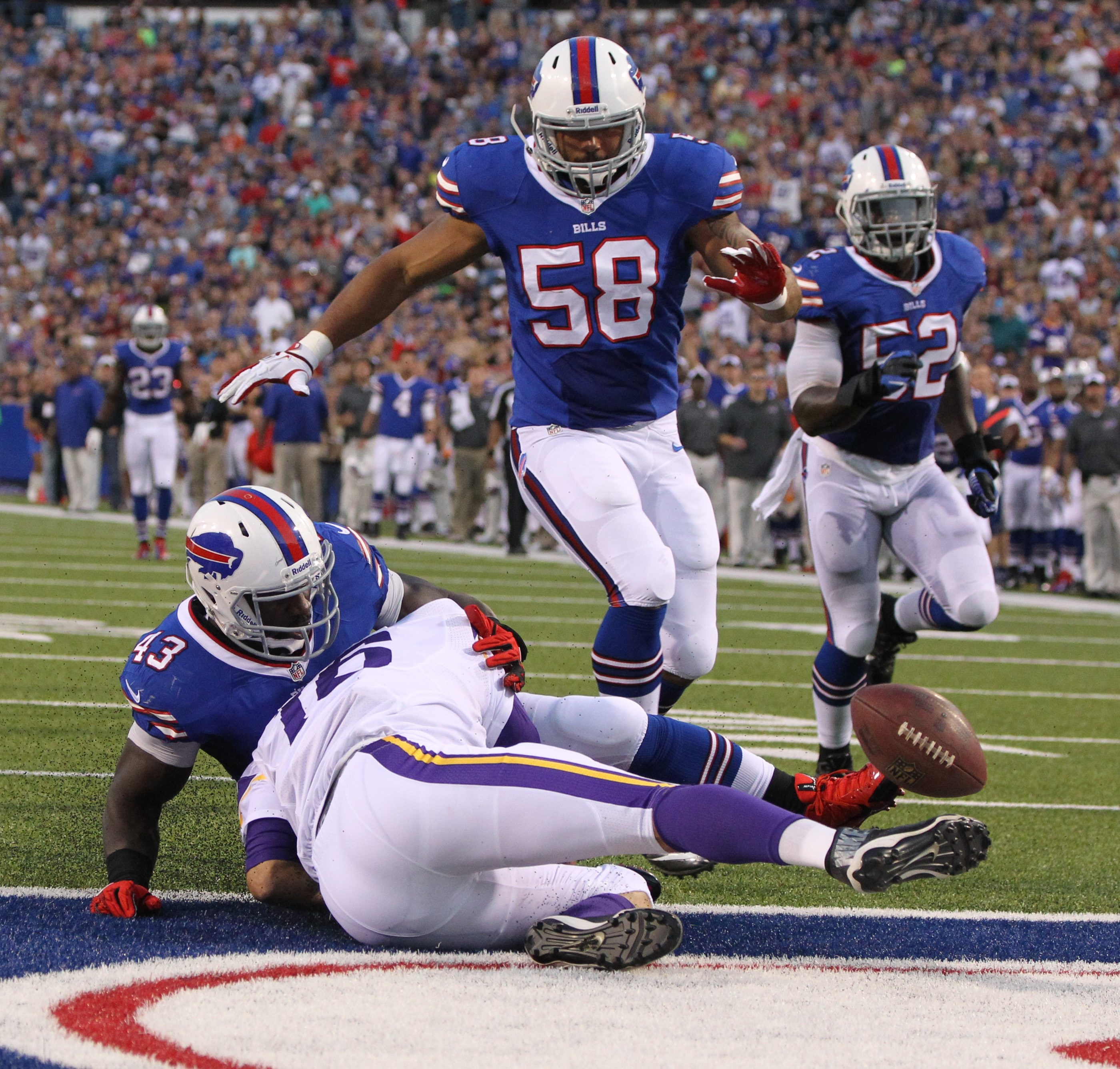 Vikings quarterback Matt Cassel fumbles the snap and Bills linebacker Bryan Scott keeps Cassel pinned down while Bills defensive end Jamie Blatnick comes in to scoop up the ball for a touchdown in the second quarter.