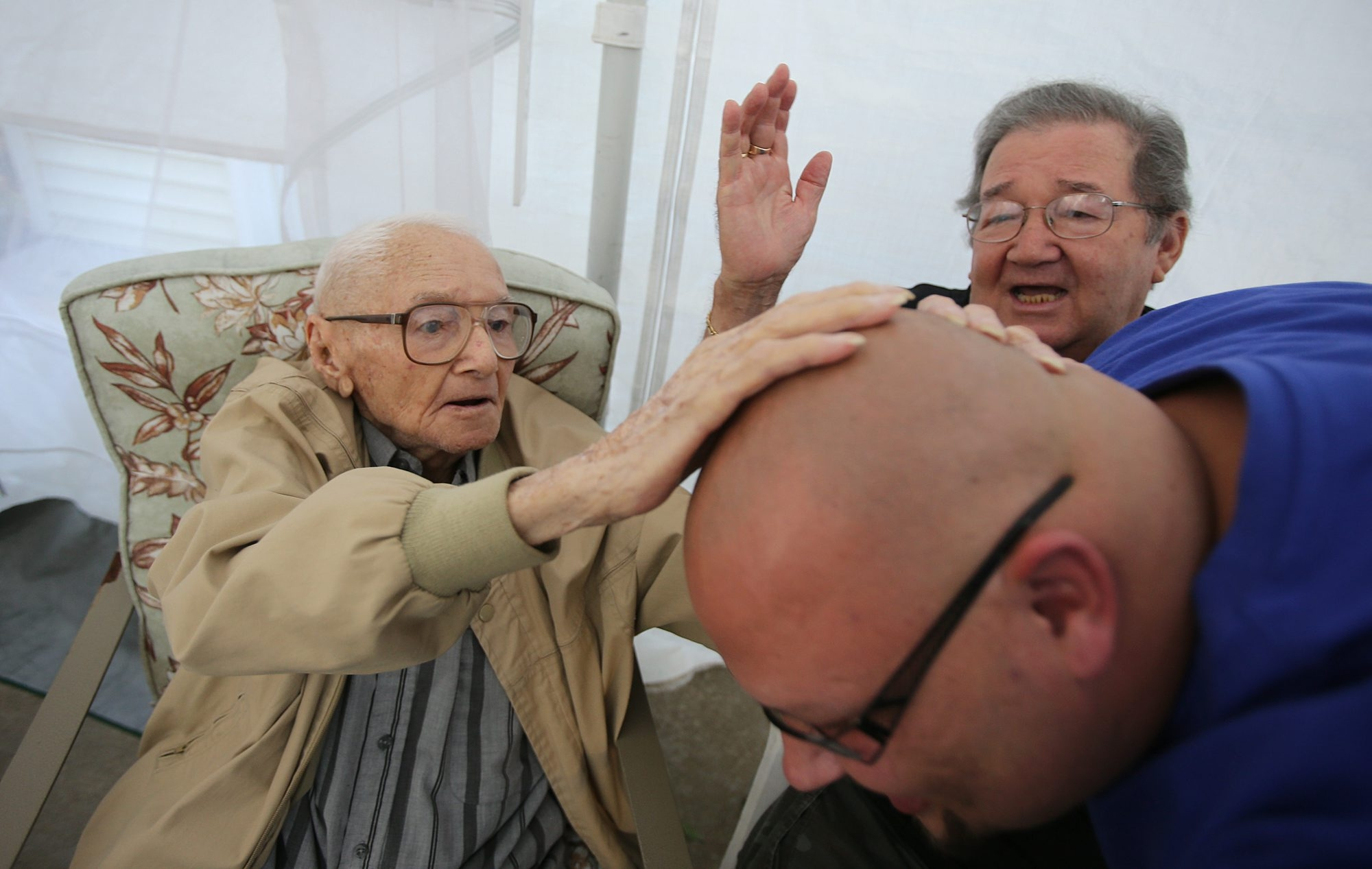 Enrique Padilla, left, rubs the head of his grandson Mike Borzillieri as his son Enrique Padilla Jr., right, looks on during his 100th birthday celebration at his home in South Buffalo on Thursday.