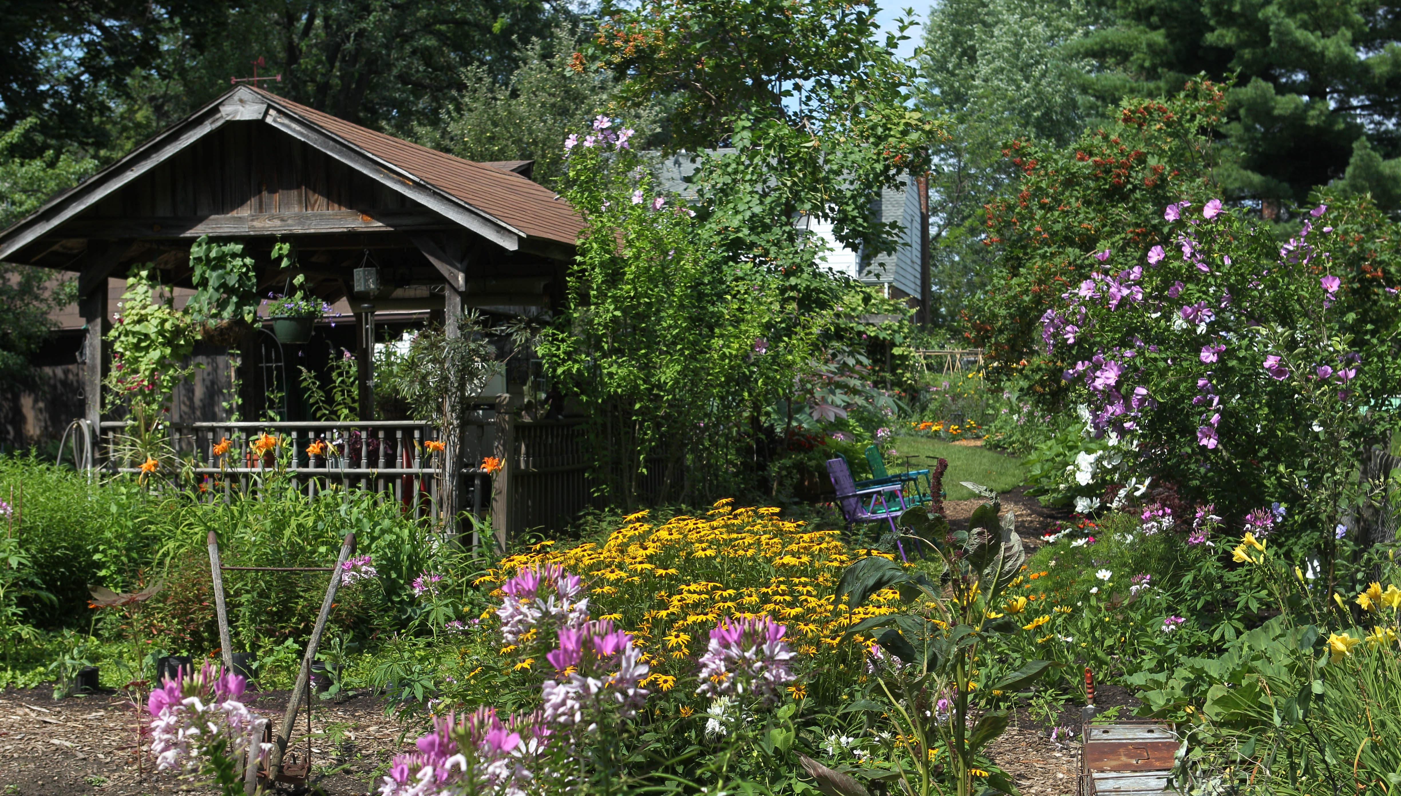 Long- and late-blooming plants and an outdoor structure enable Linda and Brian Blyth to enjoy summer well into September.