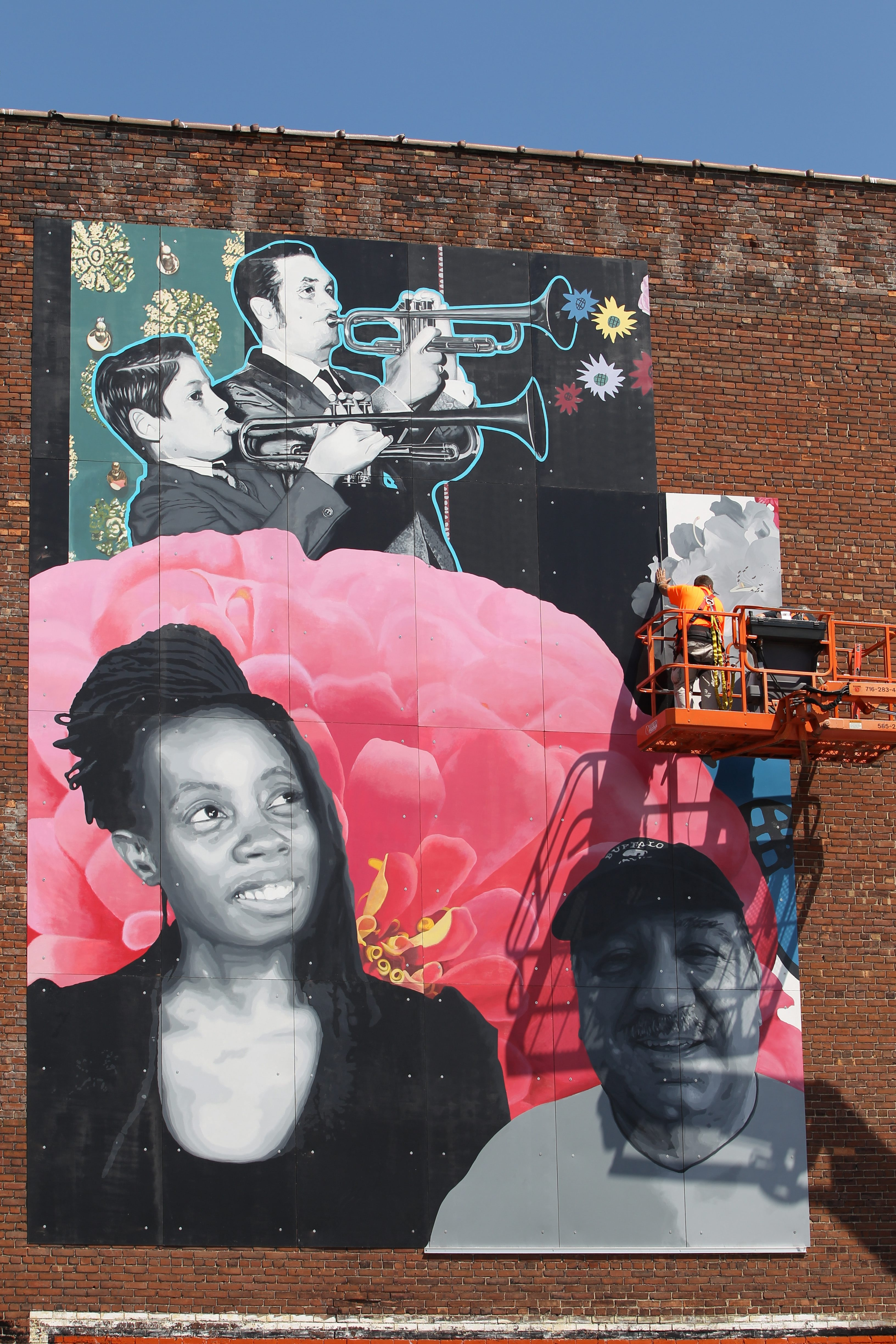 Jeff Yohe and Doug Anderson install a mural on the side of a butcher shop on Grant Street.