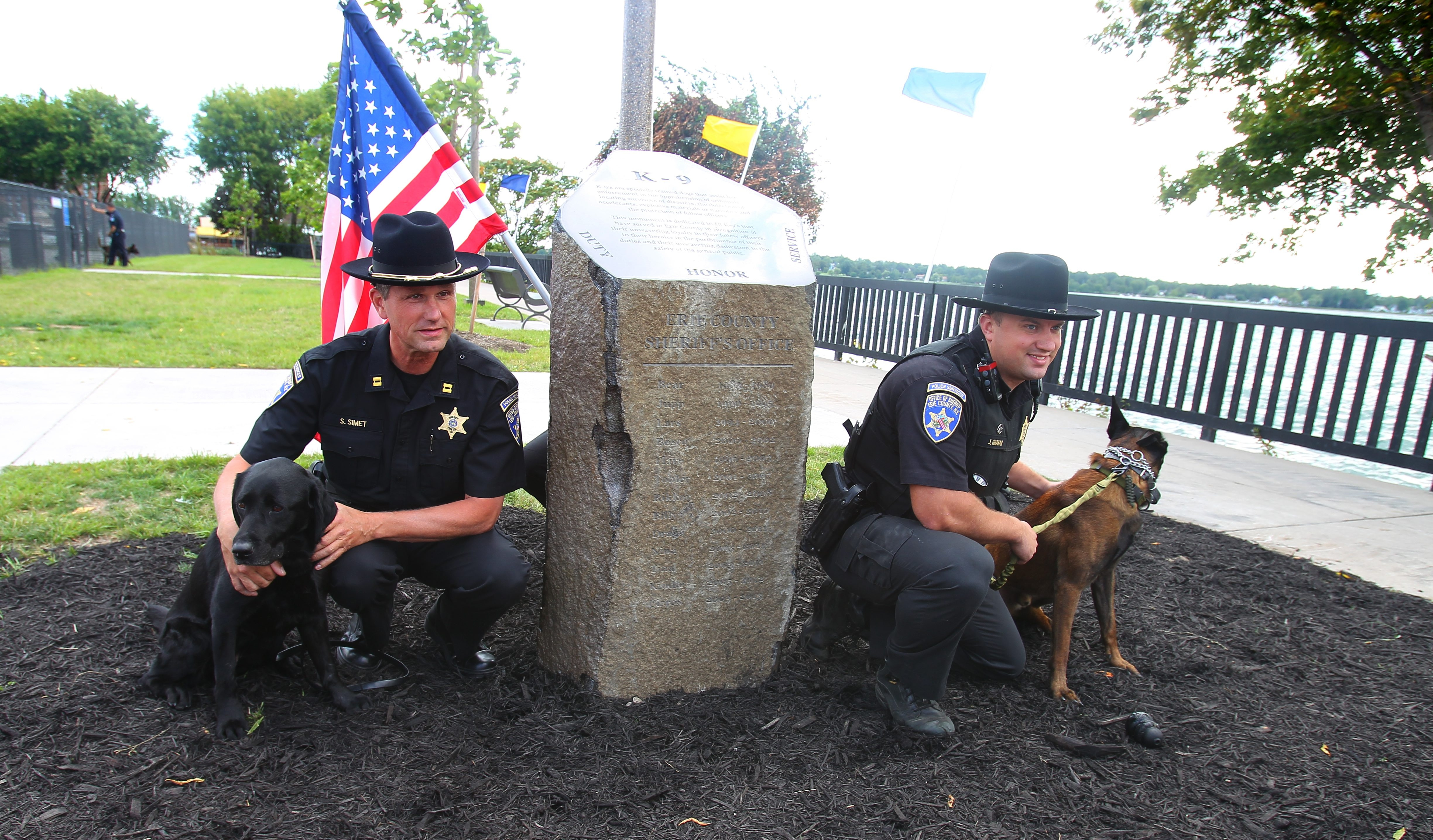 Capt. Sean Simet, with Jules, left, and Deputy Jordan Graber, with Cort, attend a dedication of a monument in Black Rock Canal Park honoring dogs in K-9 units Tuesday.