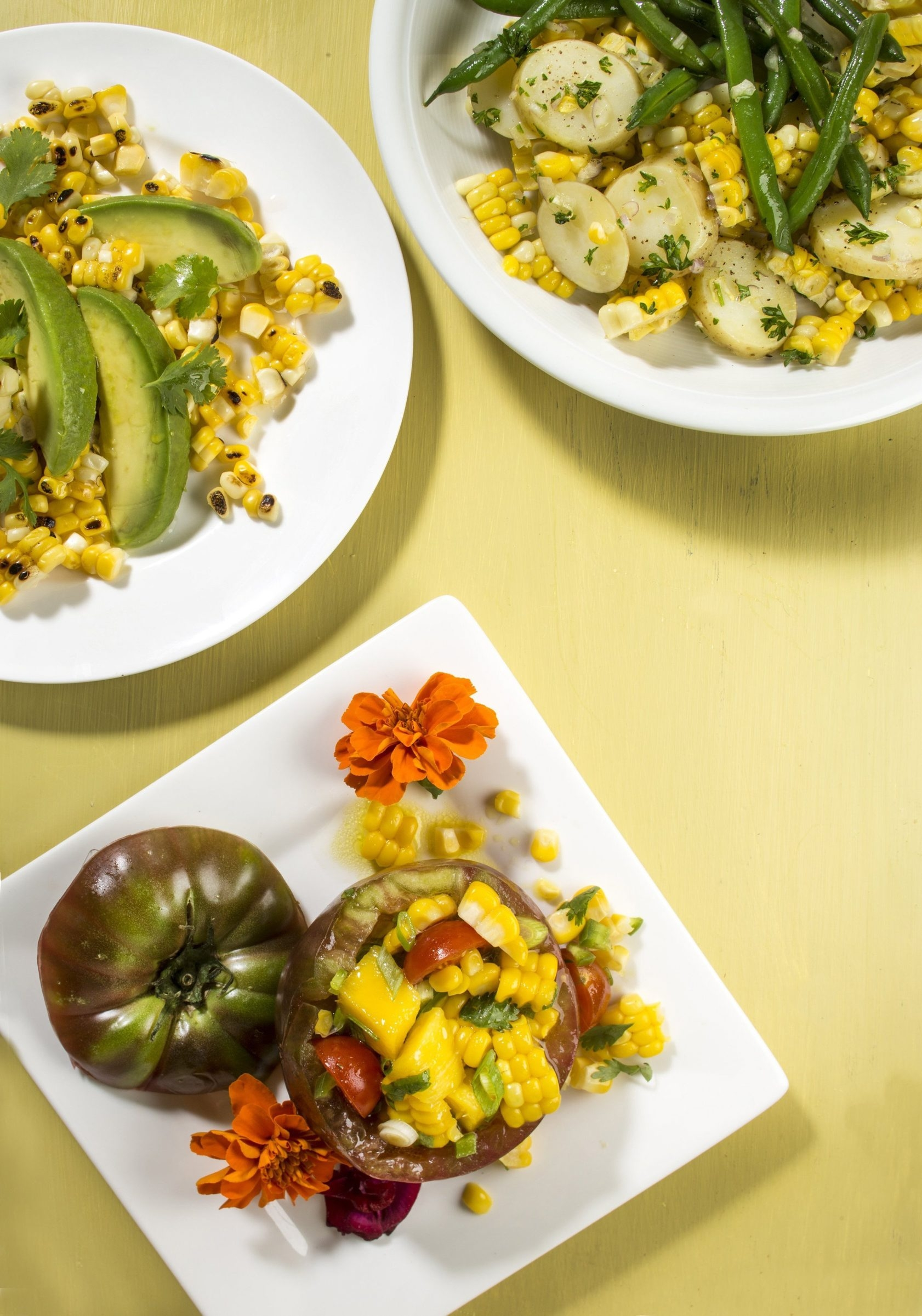 Embrace this summer's best produce and make corn salads including: corn, string bean and potato succotash salad, top right; grilled corn, avocado and cilantro, top left; and tomatoes stuffed with fresh corn and mango salad.