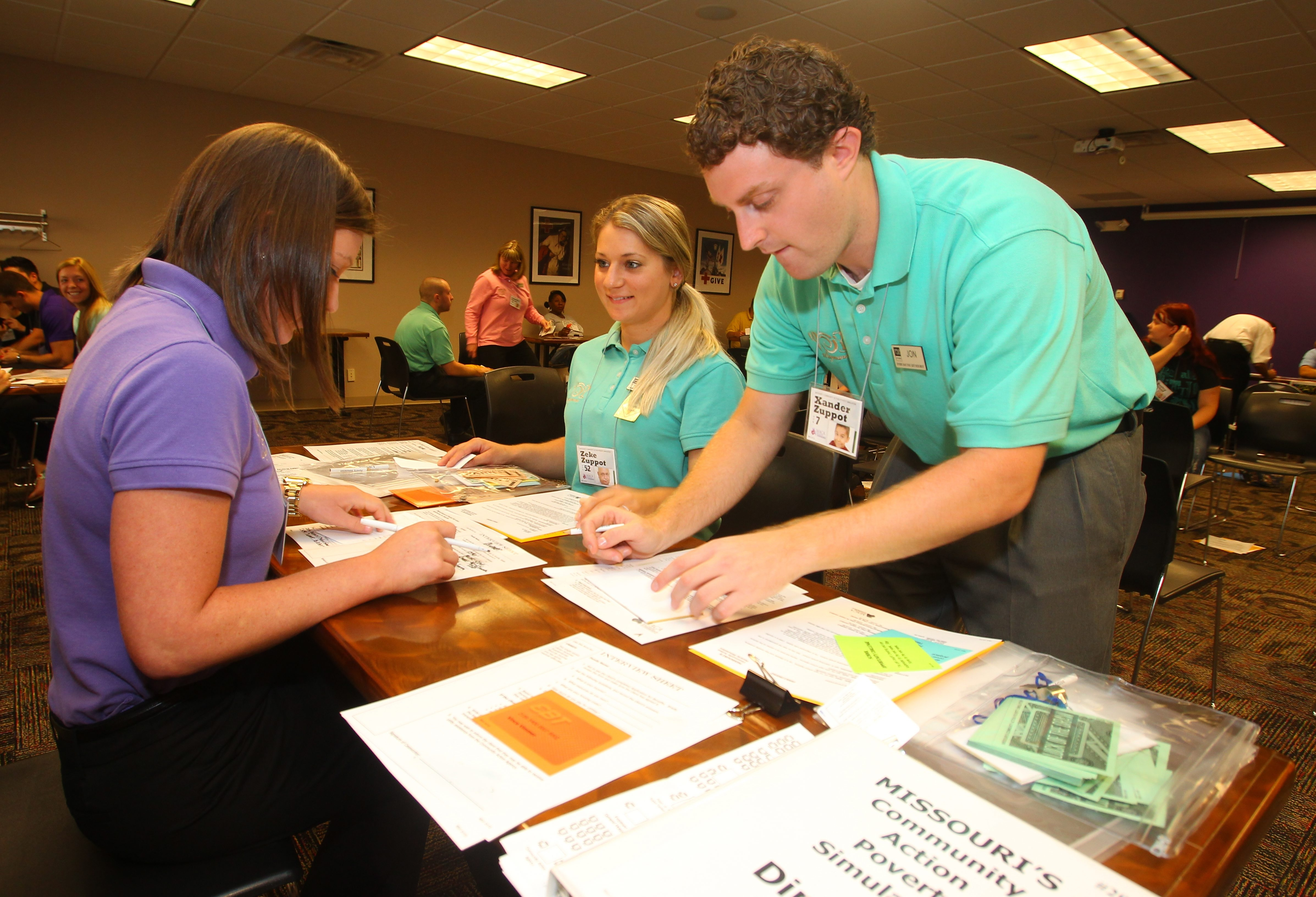 Lisa Boneberg, left, a Wegmans meat manager, plays the role of a social services case worker working with Angela D'Orazio, a Wegmans cashier, and Jon Paeplow, a Wegmans front end manager, in a workshop Monday.