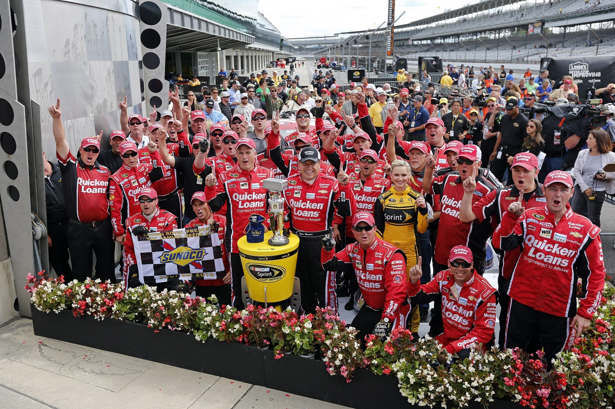 Blasdell native Jeff Kuhn, kneeling at far right in the front row, celebrates his team's victory at Indianapolis Motor Speedway after Ryan Newman won this year's Brickyard 400.
