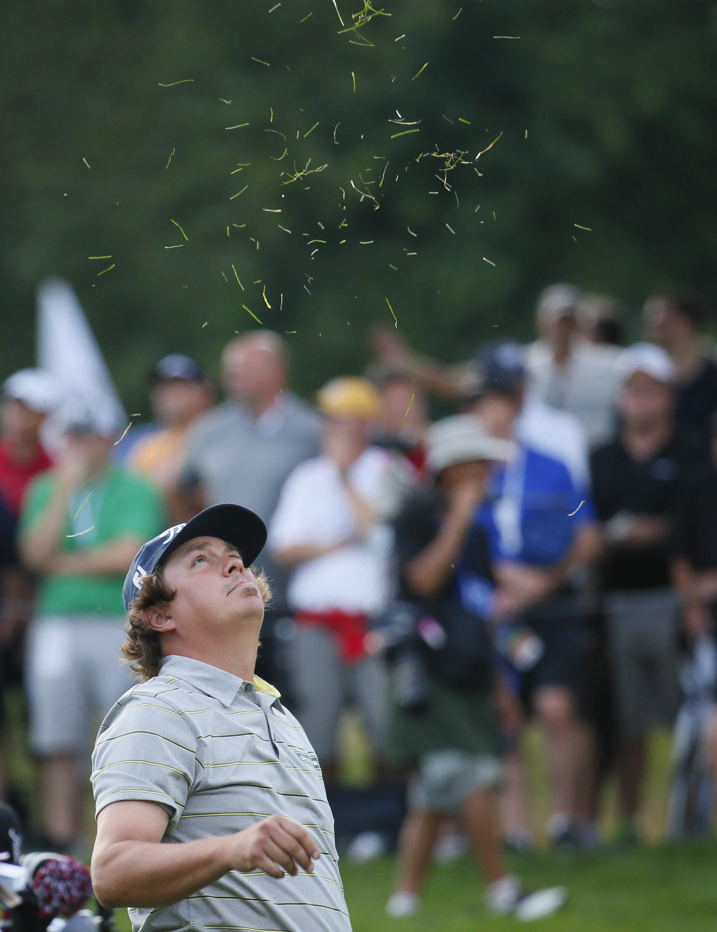 Jason Dufner tosses grass into the air to check the wind before hitting a shot on the 18th hole on Friday.