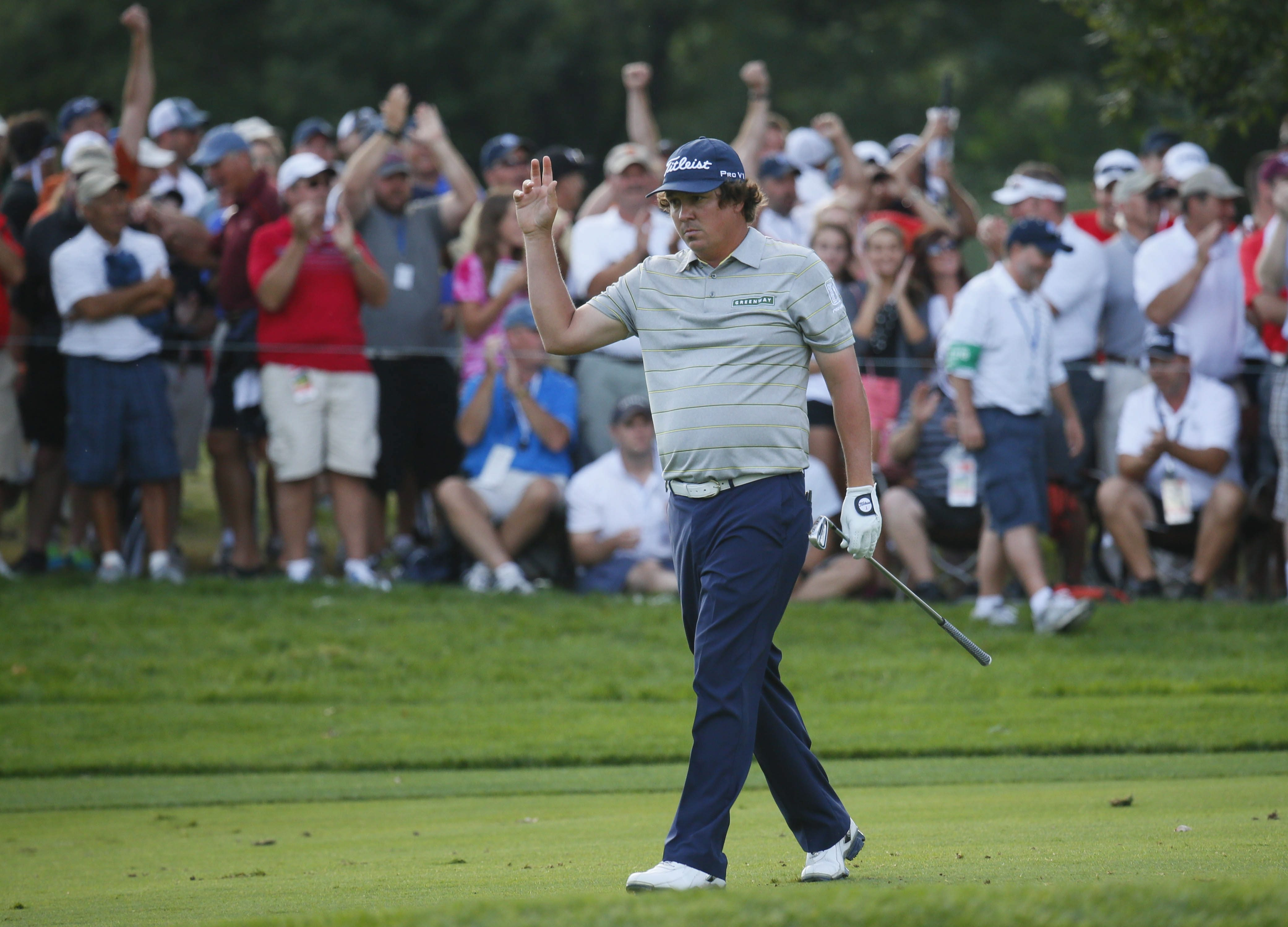 Jason Dufner waves to the cheering crowd during the walk onto the 18th green, en route to his course-record 63 during the second round Friday.