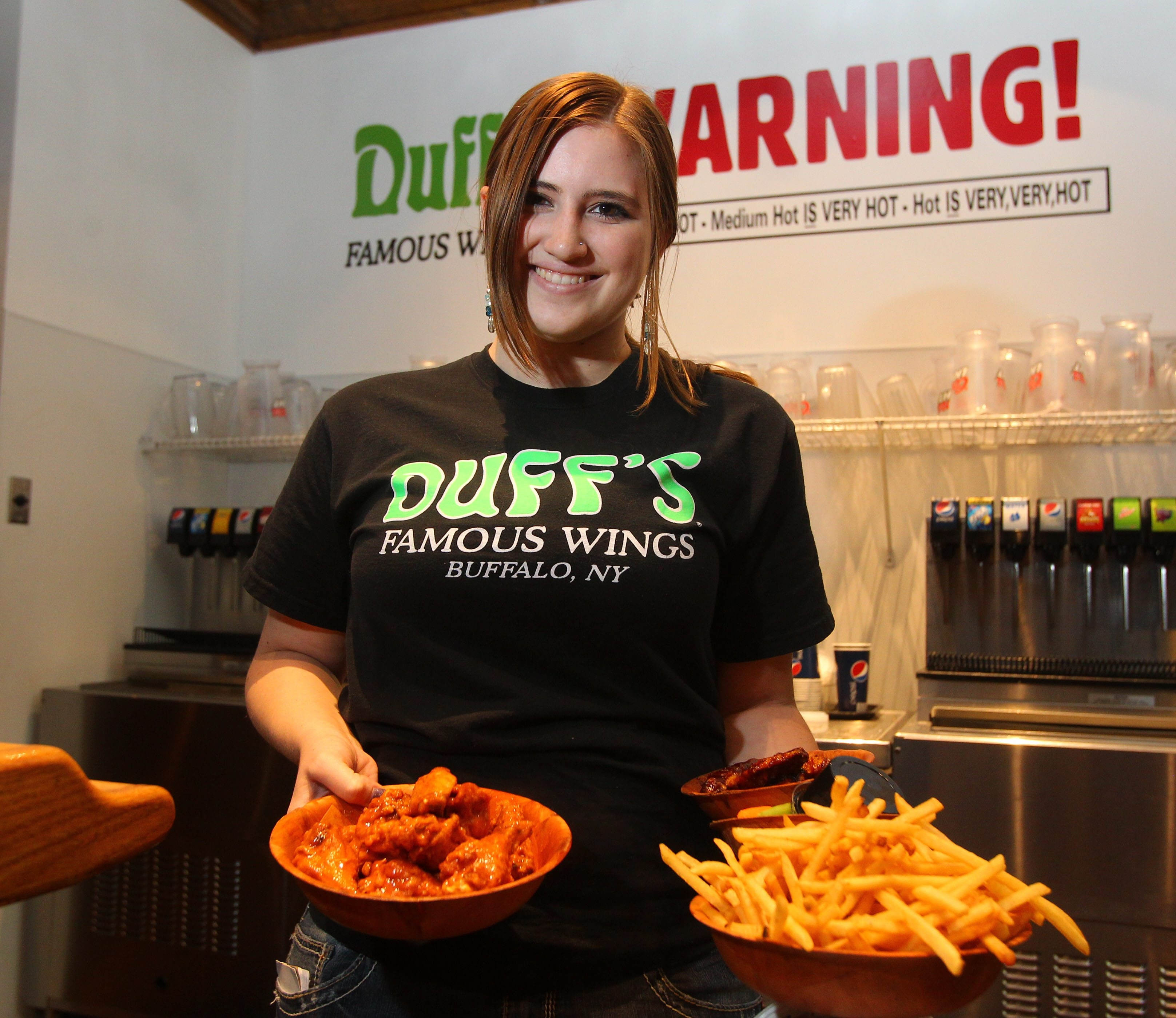 Server Tricia Faxlanger displays wings and fries at Duff's in the Eastern Hills Mall.