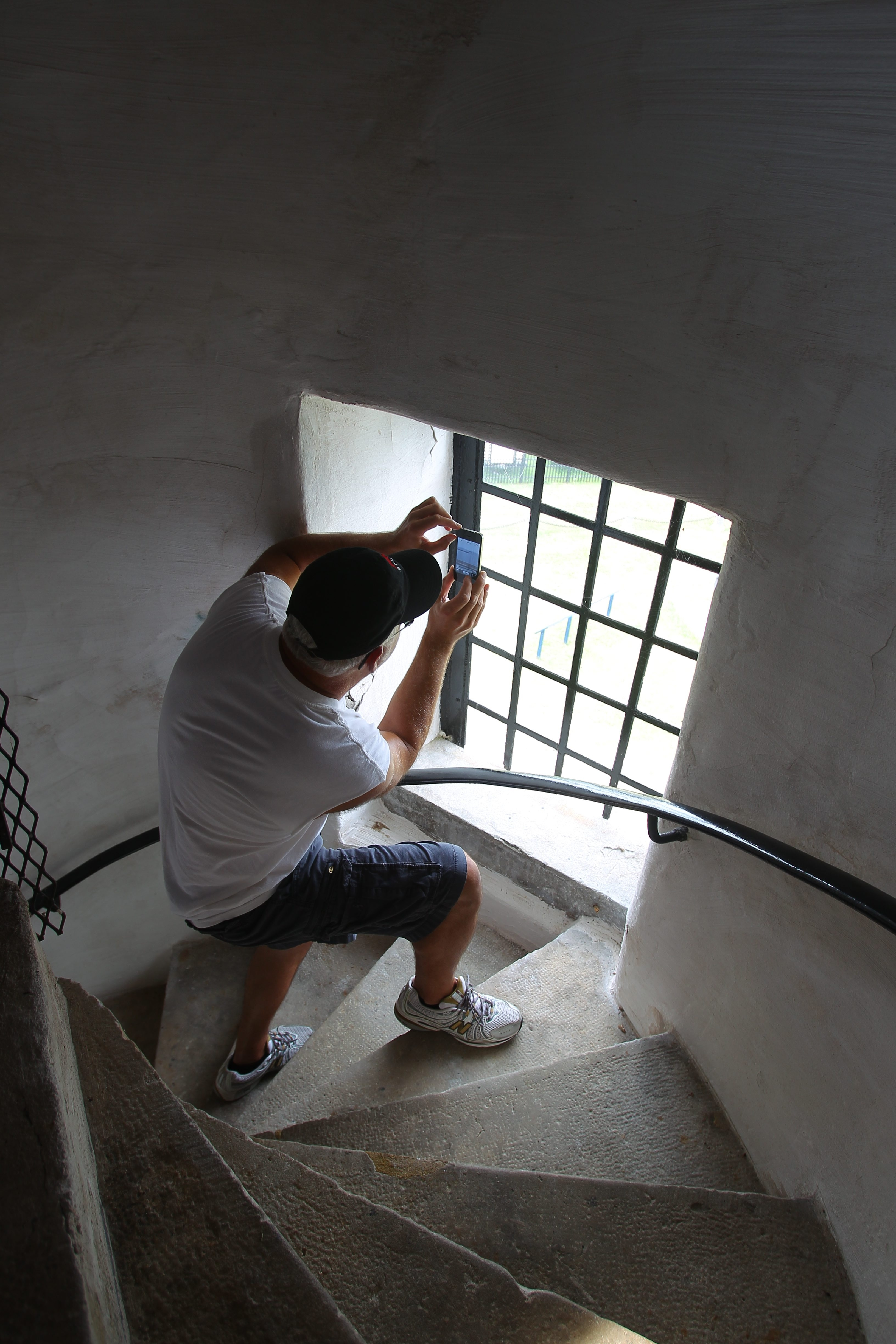 Dennis Rich  of West Seneca  takes a photo from a window on the spiral staircase of the  1833 lighthouse, shown at left,  opened to the public after renovations.