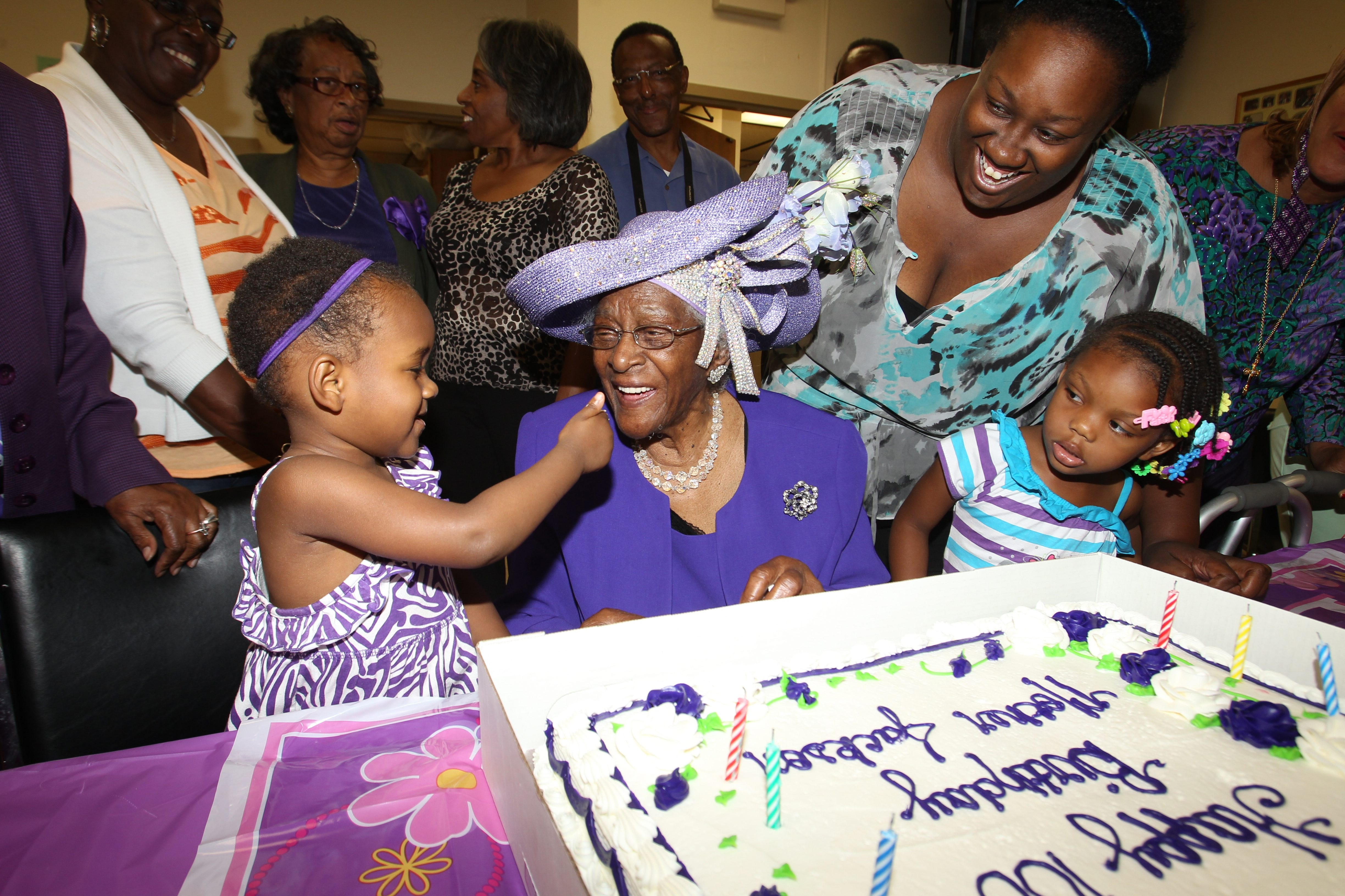 Aynna Jones gives a piece of frosting to her great, great, great-aunt Amanda Corrine Pugh Jackson as friends and family cheer her on at Jackson's 100th birthday party. See a photo gallery at BuffaloNews.com.