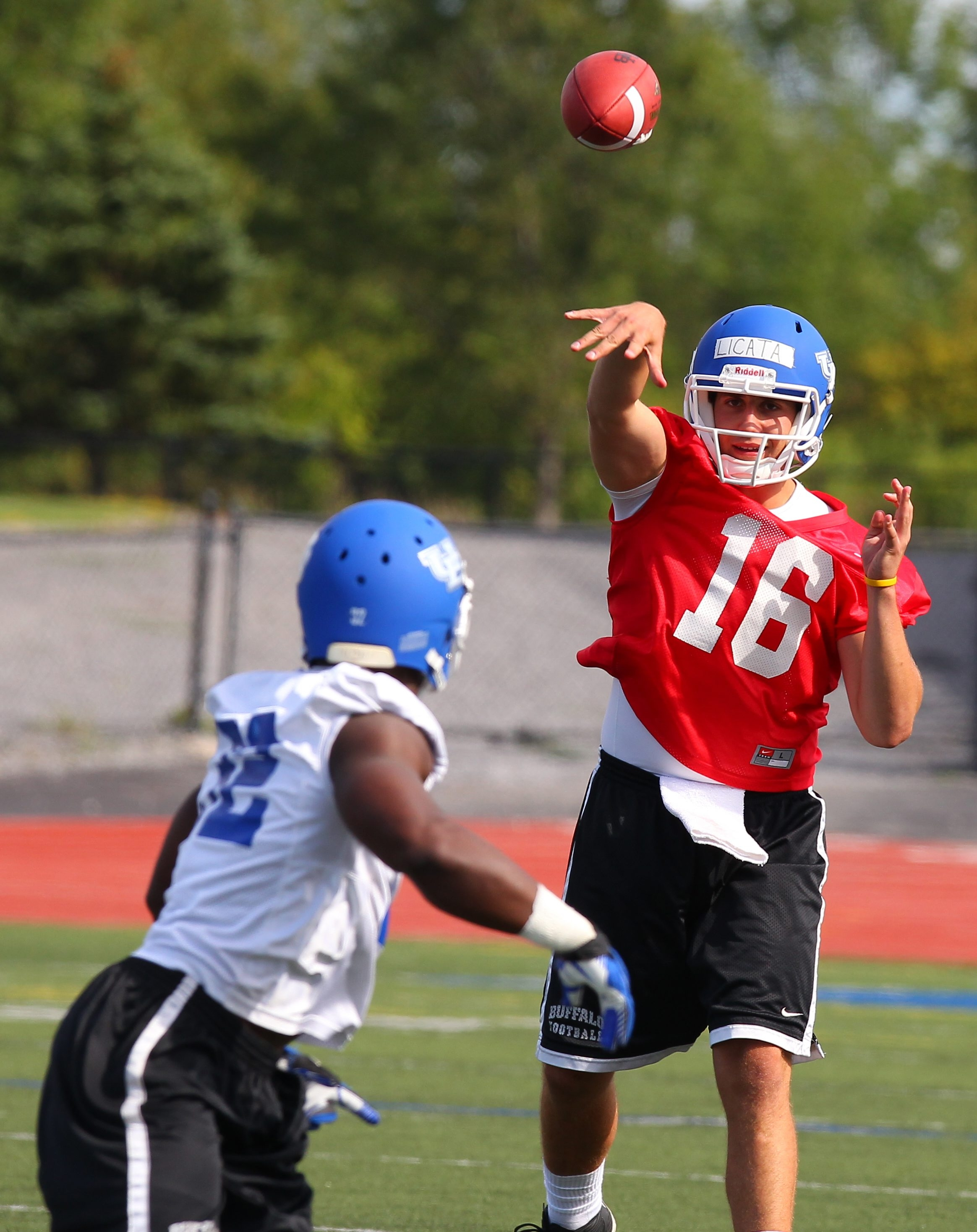 UB quarterback  Joe Licata throws a pass to running back Branden Oliver on opening day of camp.