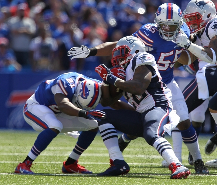 The Bills' Leodis McKelvin, left, and Jerry Hughes stop the Patriots' Stevan Ridley on a disputed play in the  first quarter. (Mark Mulville/Buffalo News)