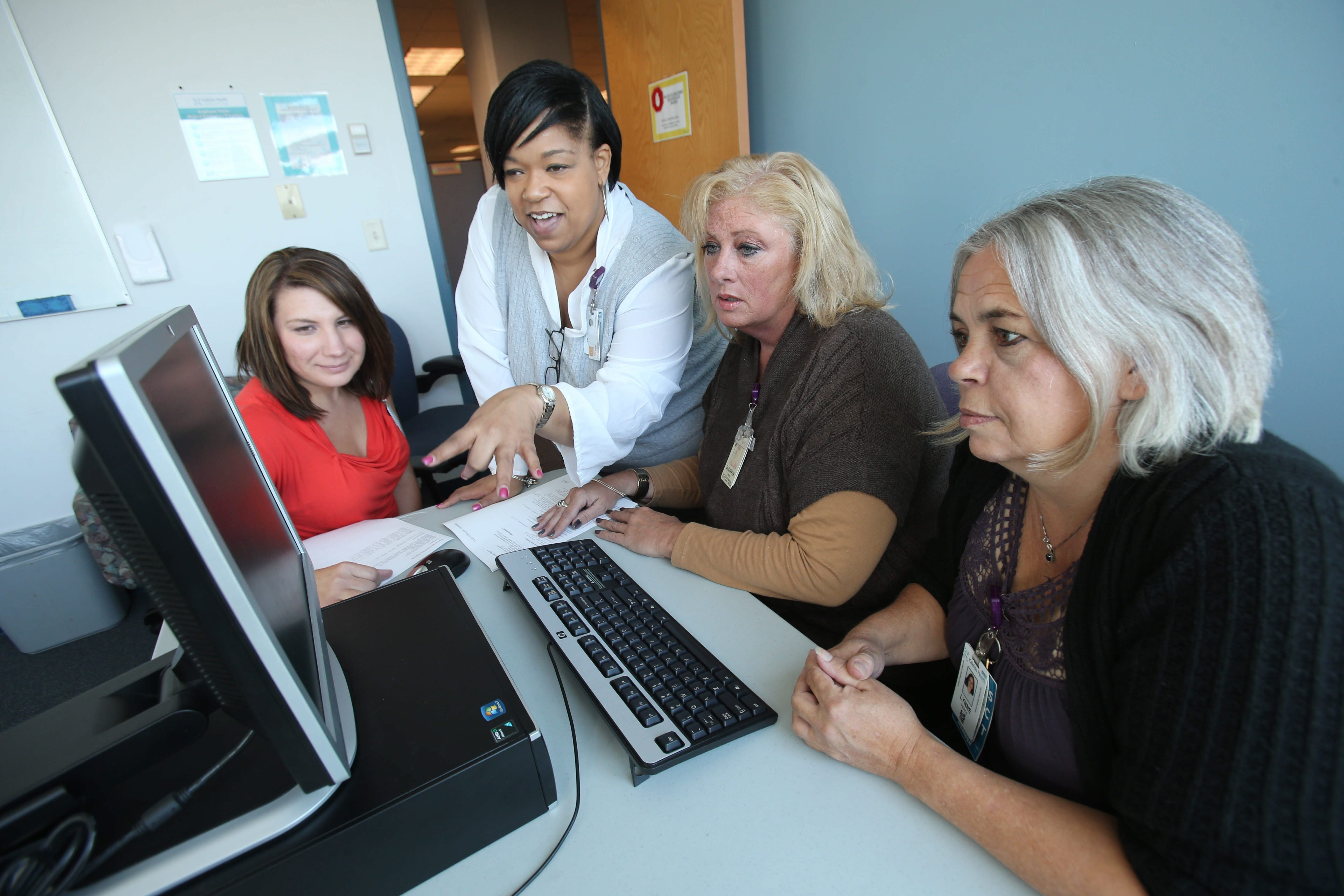 From left, Rachael Sinicki, patient representative, Simmone Washington, manager of financial counseling services, Elizabeth Driscoll, navigator, and Lynne Pierce, patient representative, take part in a training session Friday at the Larkin at Exchange Building.