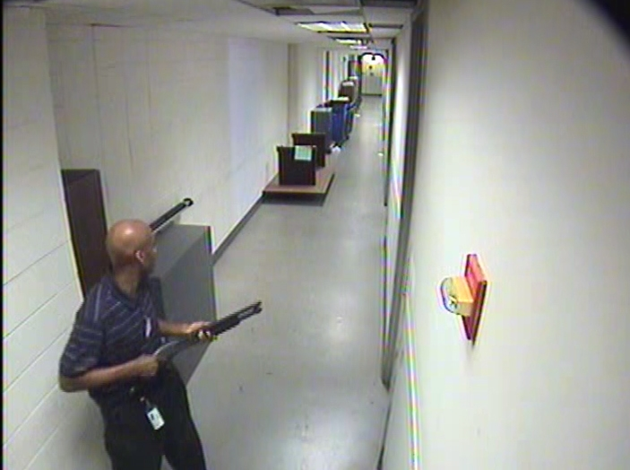 Aaron Alexis, armed with a shotgun, is shown on surveillance video moving through the hallways of Building 197 during his Washington Navy Yard rampage on Sept. 16.