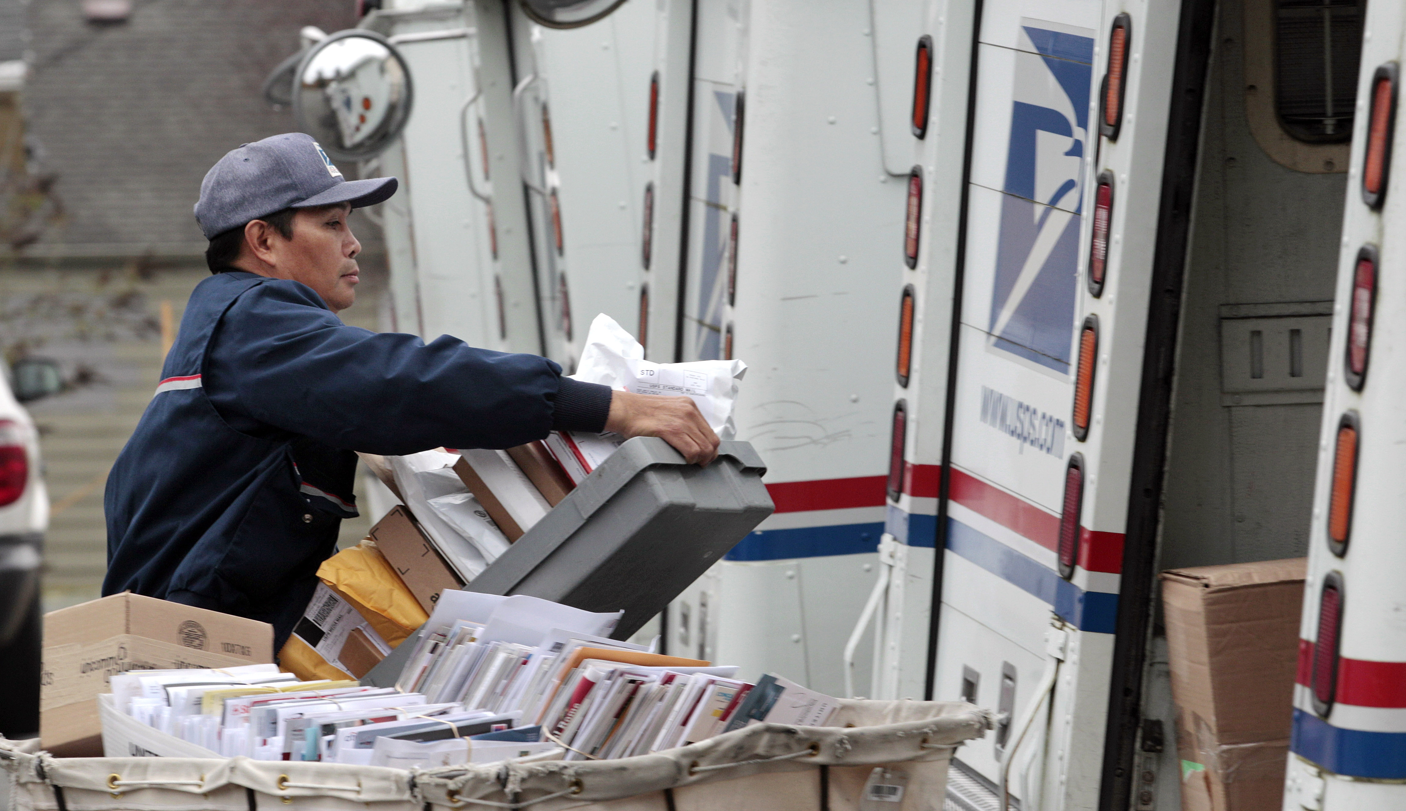 A letter carrier moves boxes of mail into his truck to begin delivery at a post office. (AP Photo/Elaine Thompson, File)