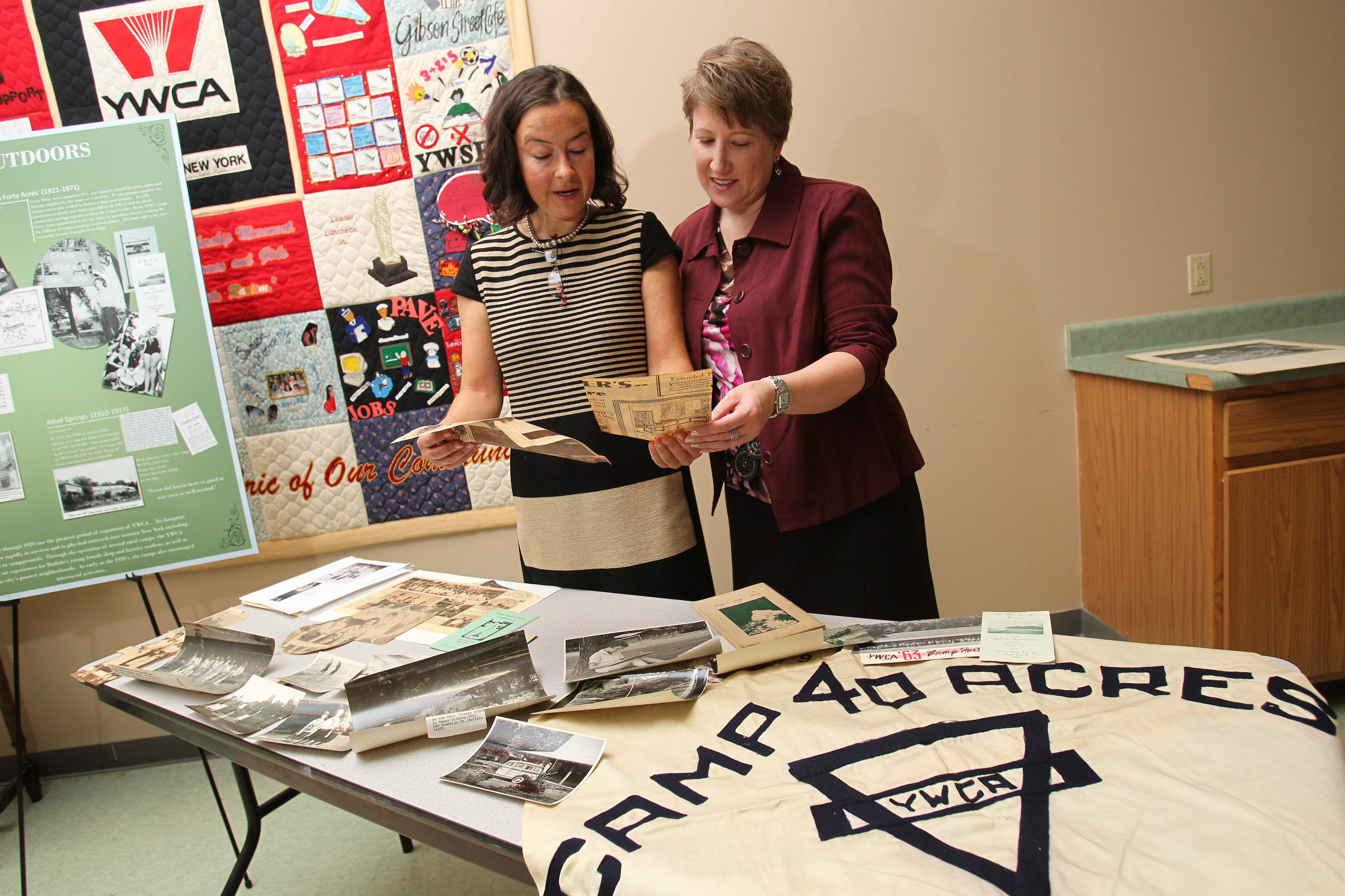 Deborah Lynn Williams, left, CEO of YWCA of Western New York, and Nadine DiStefano, public relations and event consultant  for the Y, look at old photos from Camp Forty Acres on Thursday.
