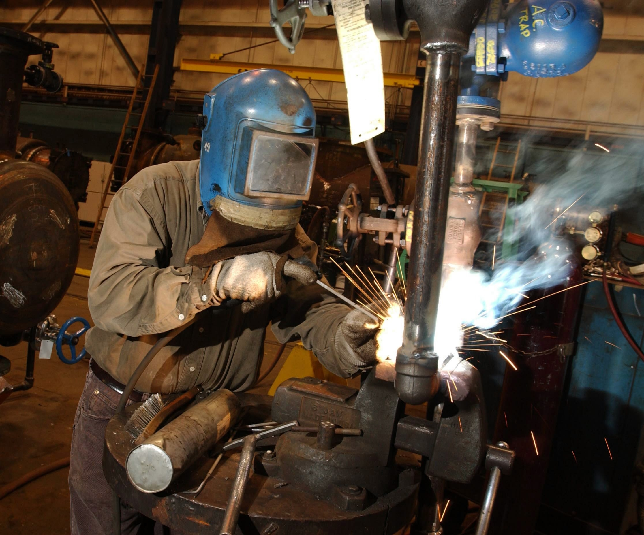 A welder at Graham Corp. works on piping. The company recently landed three large contracts.