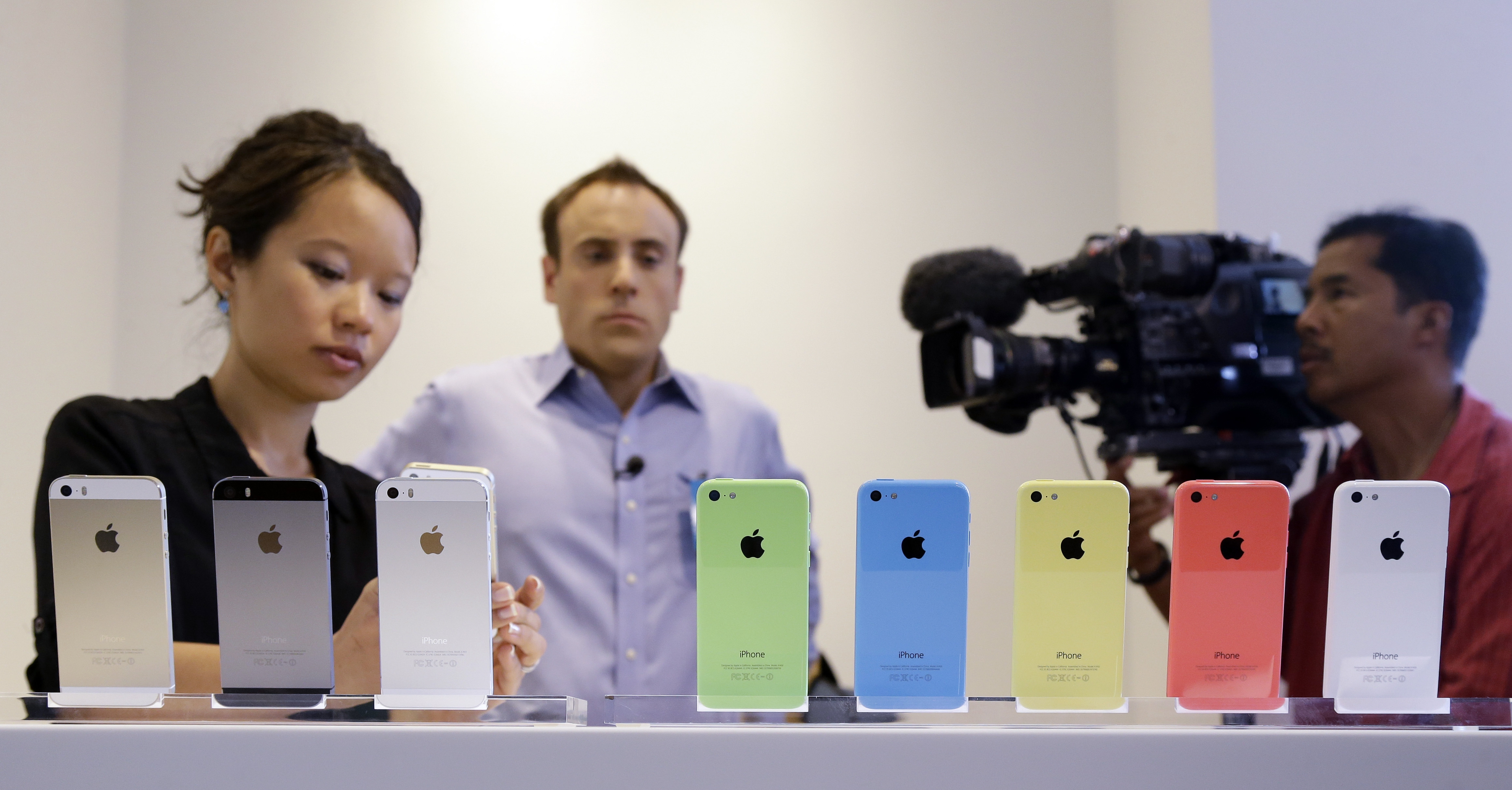 Members of the media review the new iPhone  5C and 5S during a new product announcement at Apple headquarters on Tuesday in Cupertino, Calif. Analysts criticized Apple's latest iPhones for lacking new features and for being too expensive.