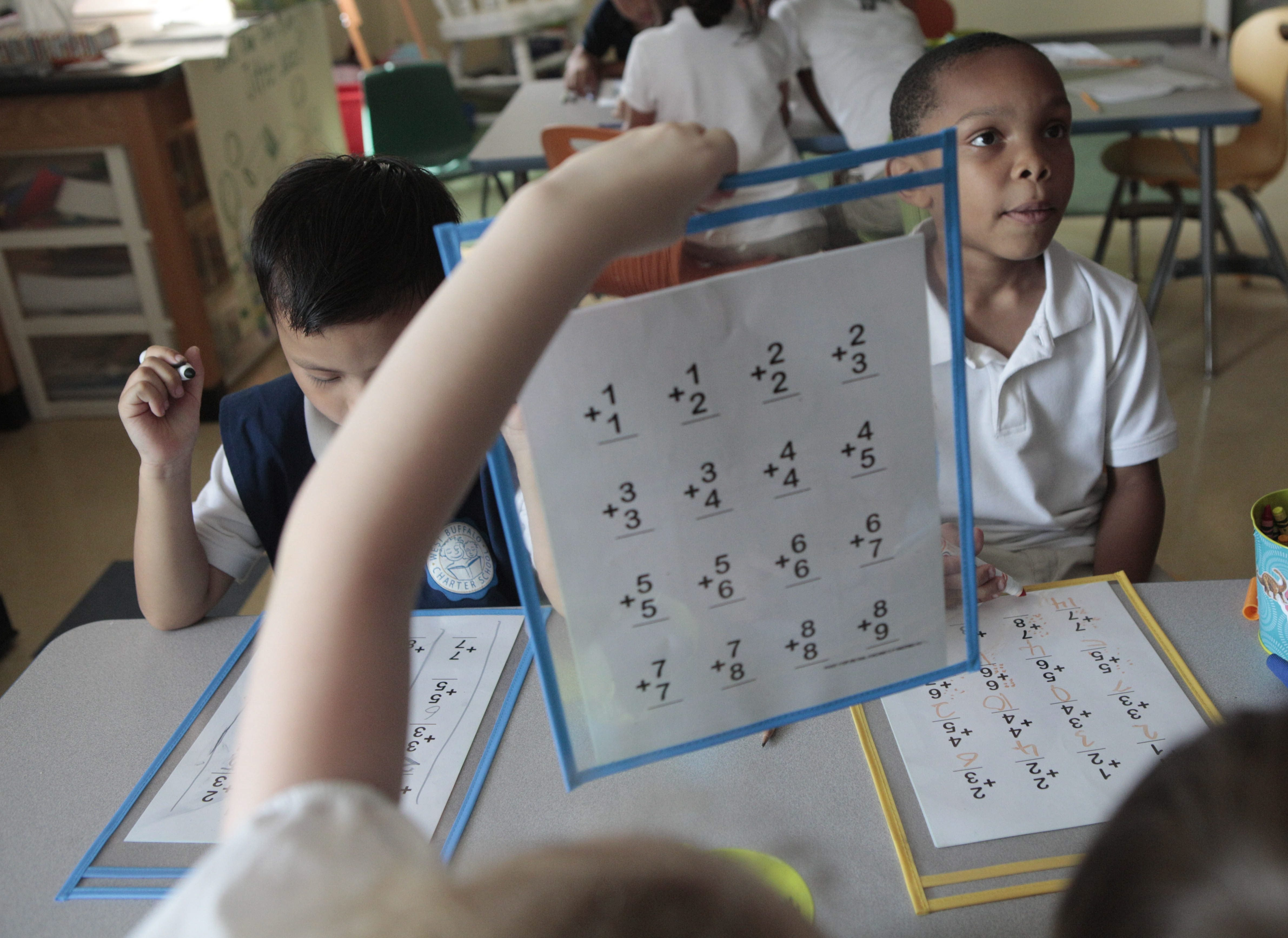 First-grade students Way Yaw Oo, left, and Ivan Rankin Jr., right, work on a math assignment at the West Buffalo Charter School on Wednesday.