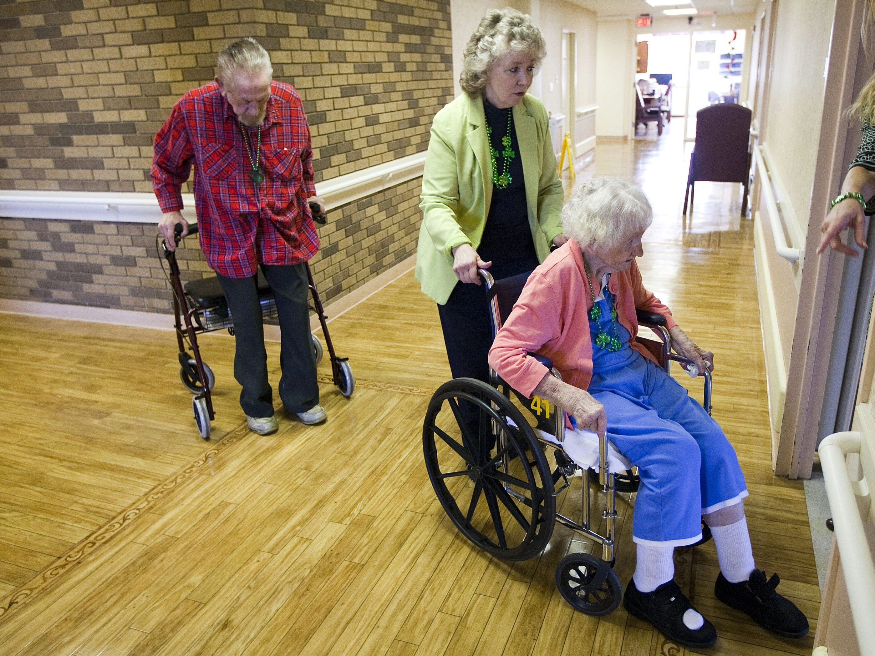 Marilyn Herrin, 68, center, assists her mother, Mary Herrin, 96, in Dallas, Texas. As the population ages, a shortage of caregivers for the elderly looms.