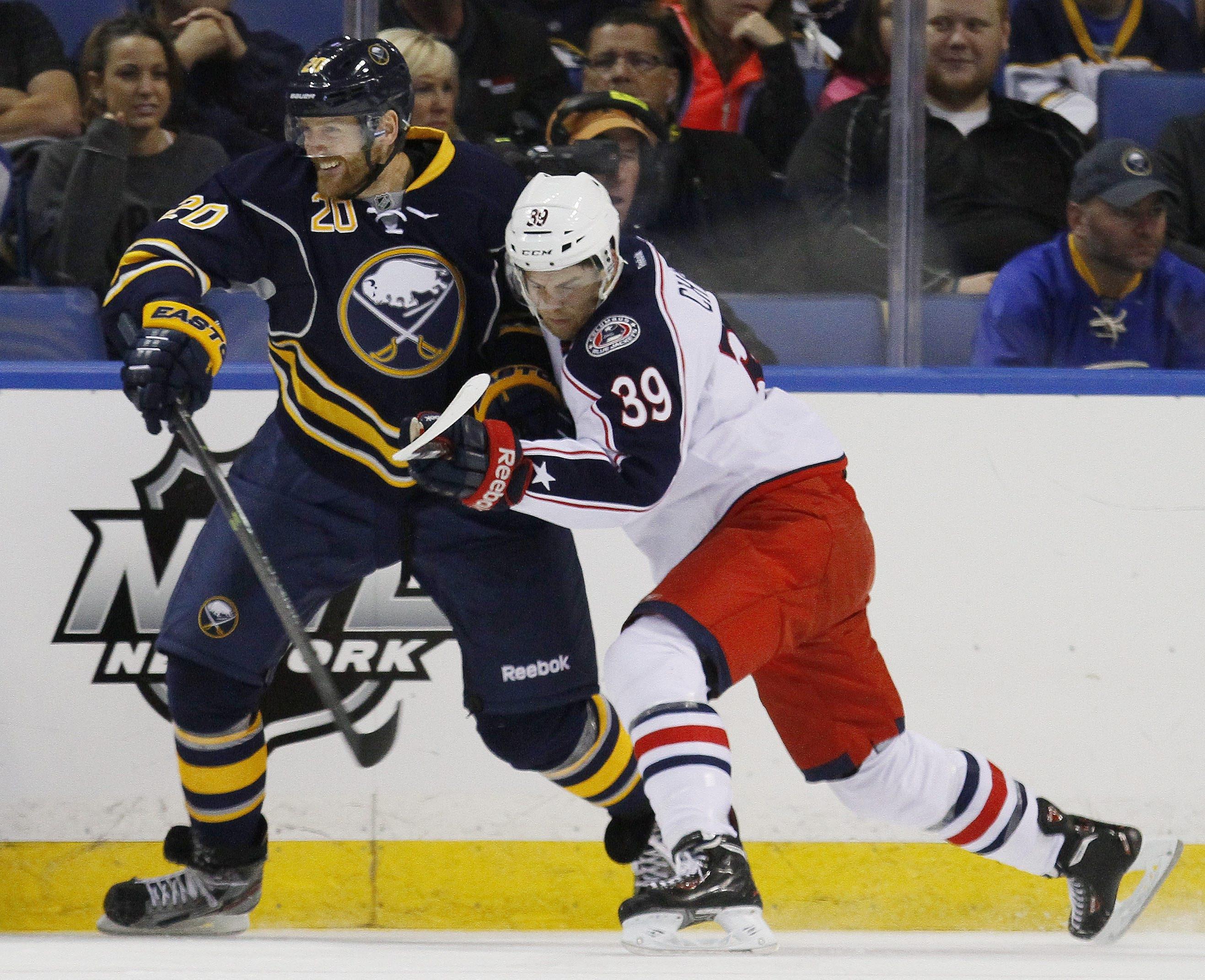 Buffalo's Henrik Tallinder battles Columbus' Michael Chaput along the boards during Wednesday night's game.