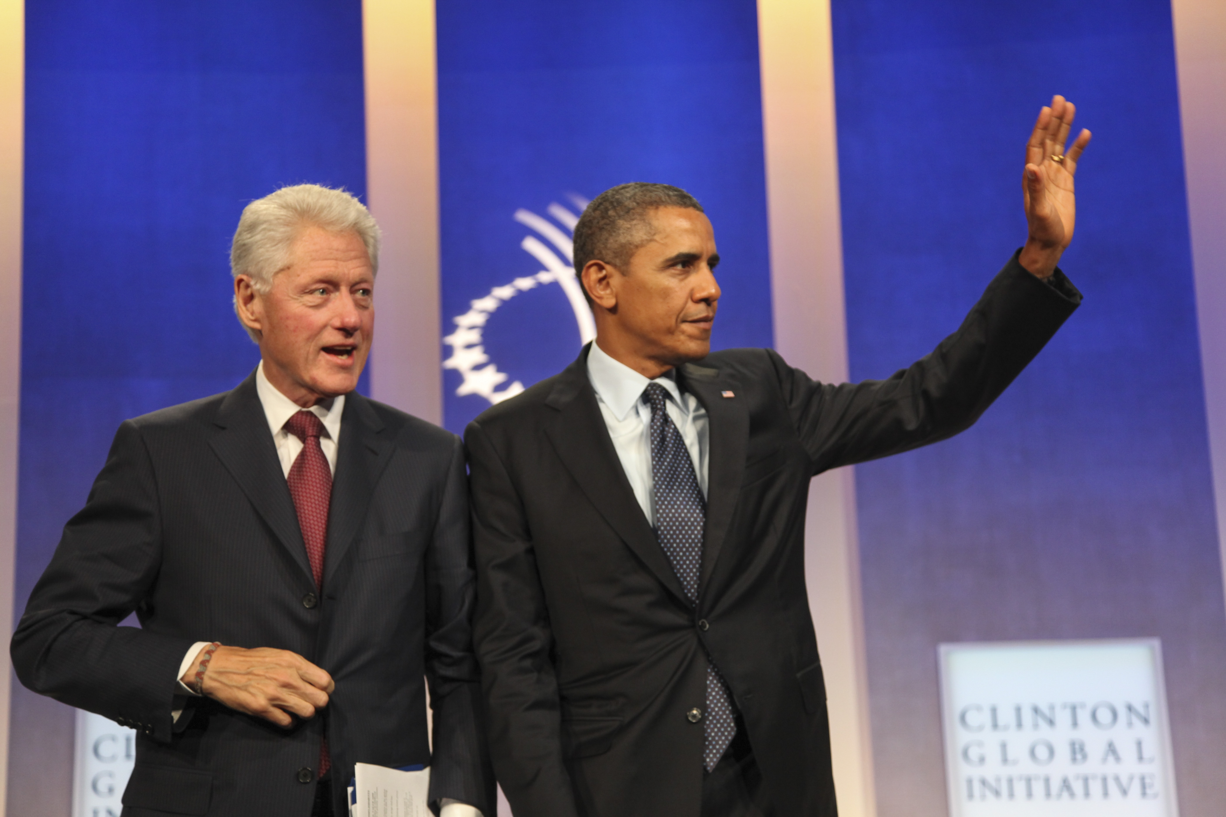 President Obama acknowledges audience as he and former President Bill Clinton go onstage to speak about health care law at meeting of Clinton Global Initiative in New York City.