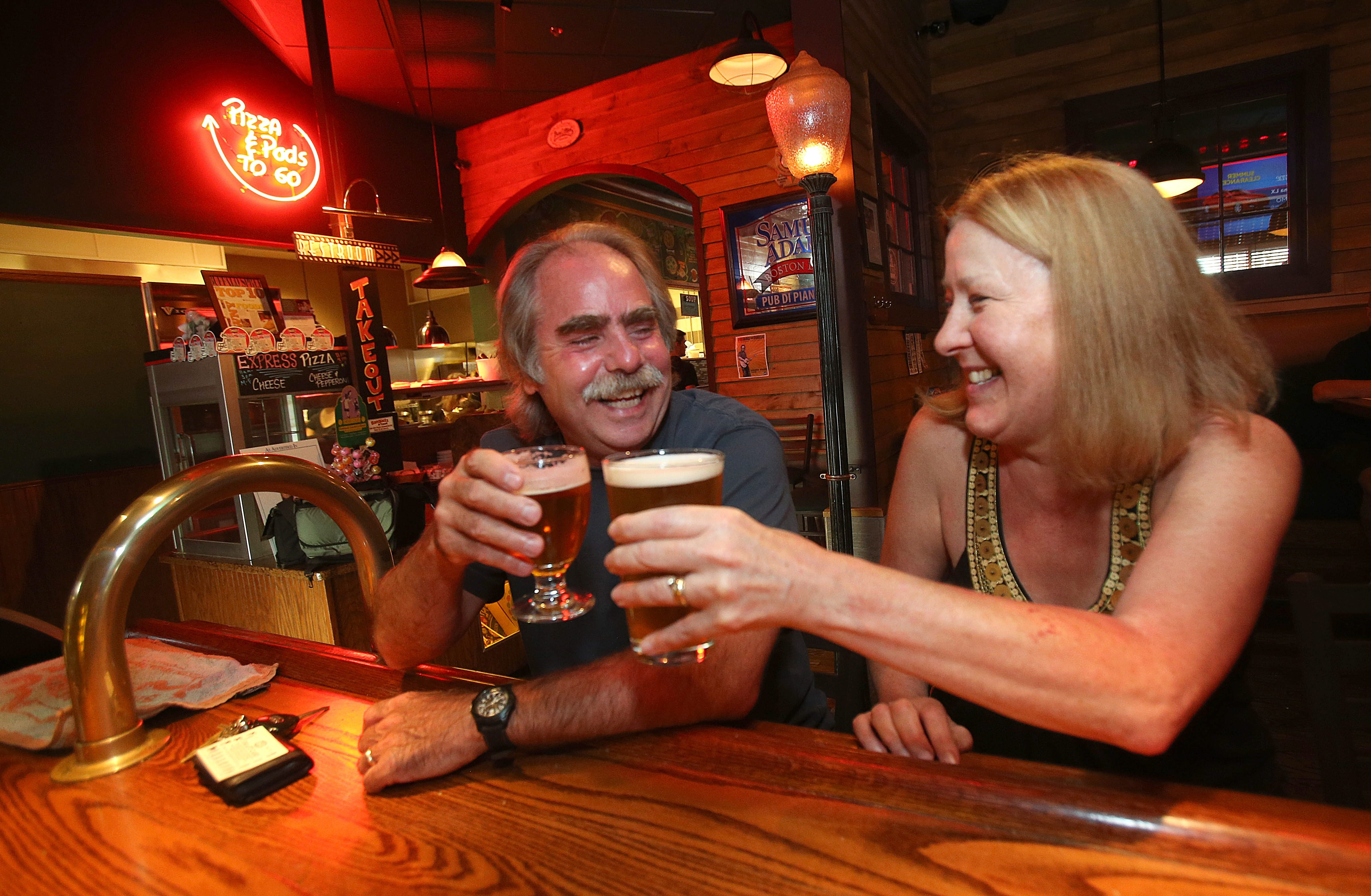 Microbrew beer fans Mike and Sylvia MacDonald of Lockport toast to their craft beer offerings at the Pizza Plant on Transit Road in Williamsville.